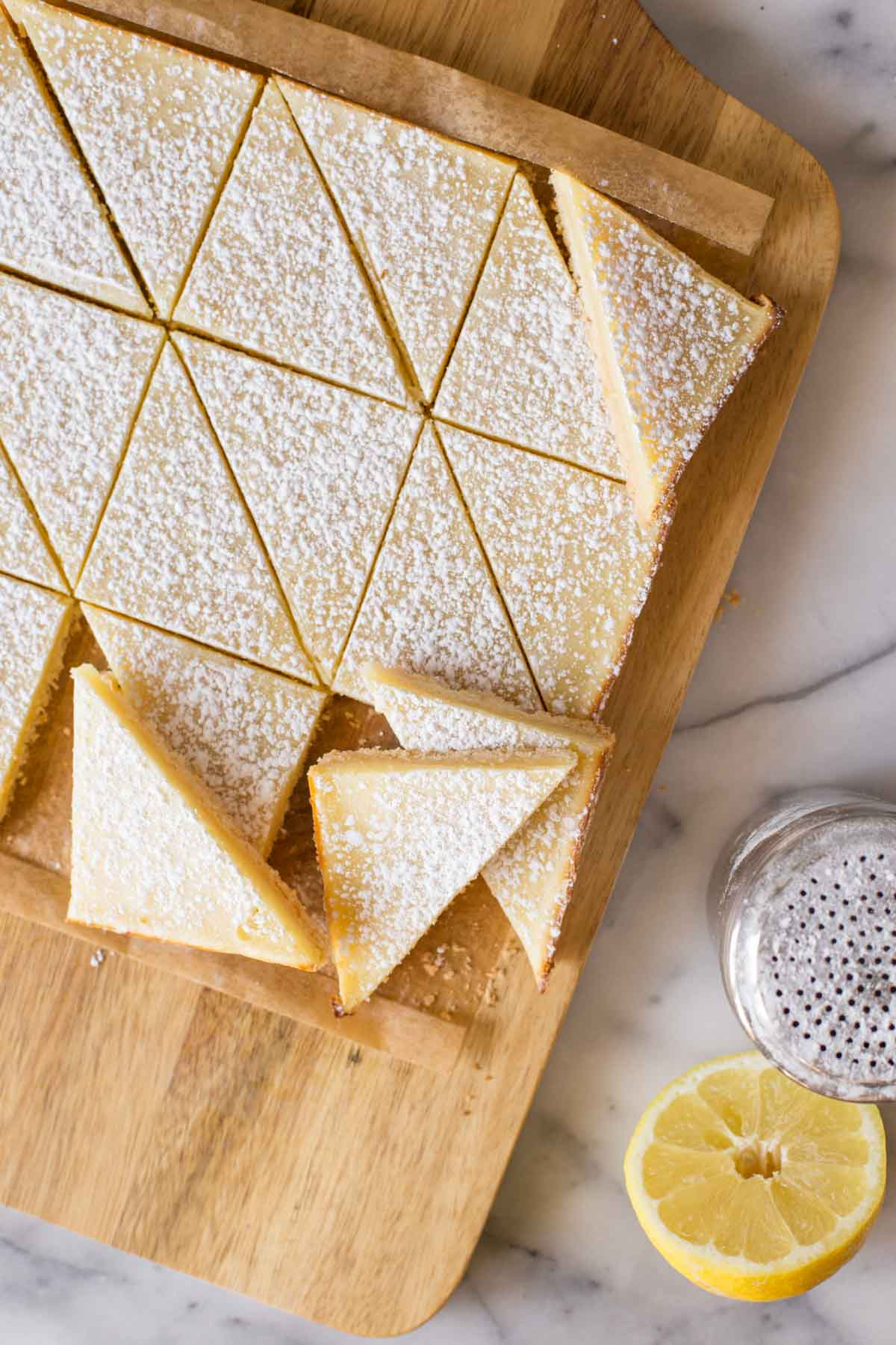 Overhead shot of cut Swedish Lemon Bars on a wooden cutting board.