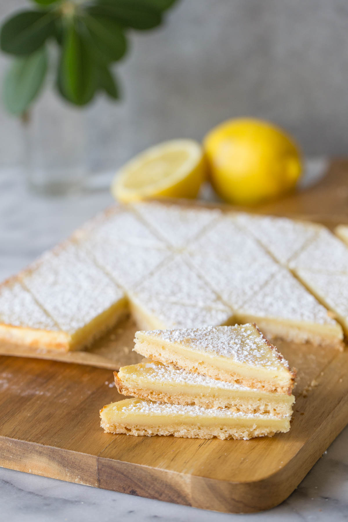 Three Swedish Lemon Bars stacked on a wooden cutting board, with more bars and lemons in the background.