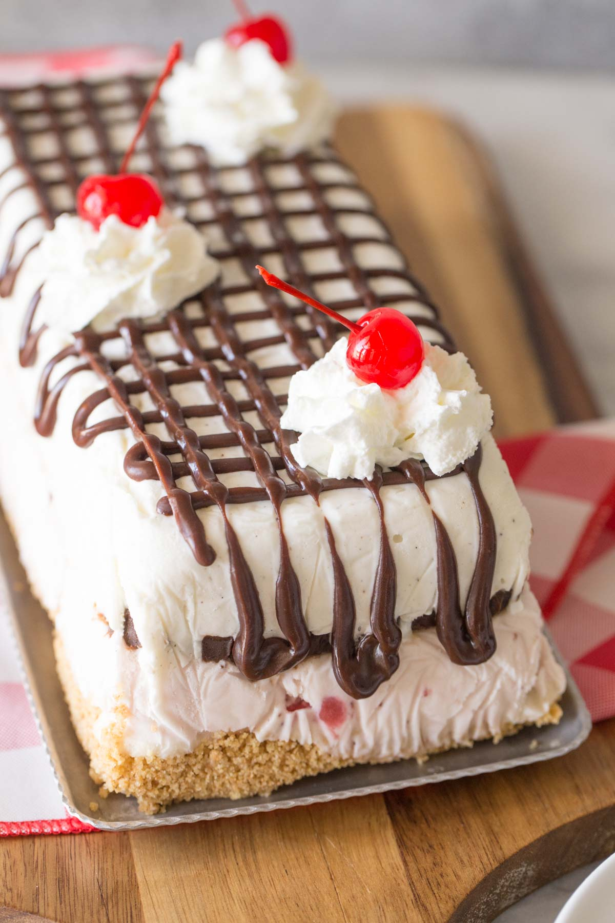 Banana Split Ice Cream Cake on a serving tray sitting on a wooden cutting board.