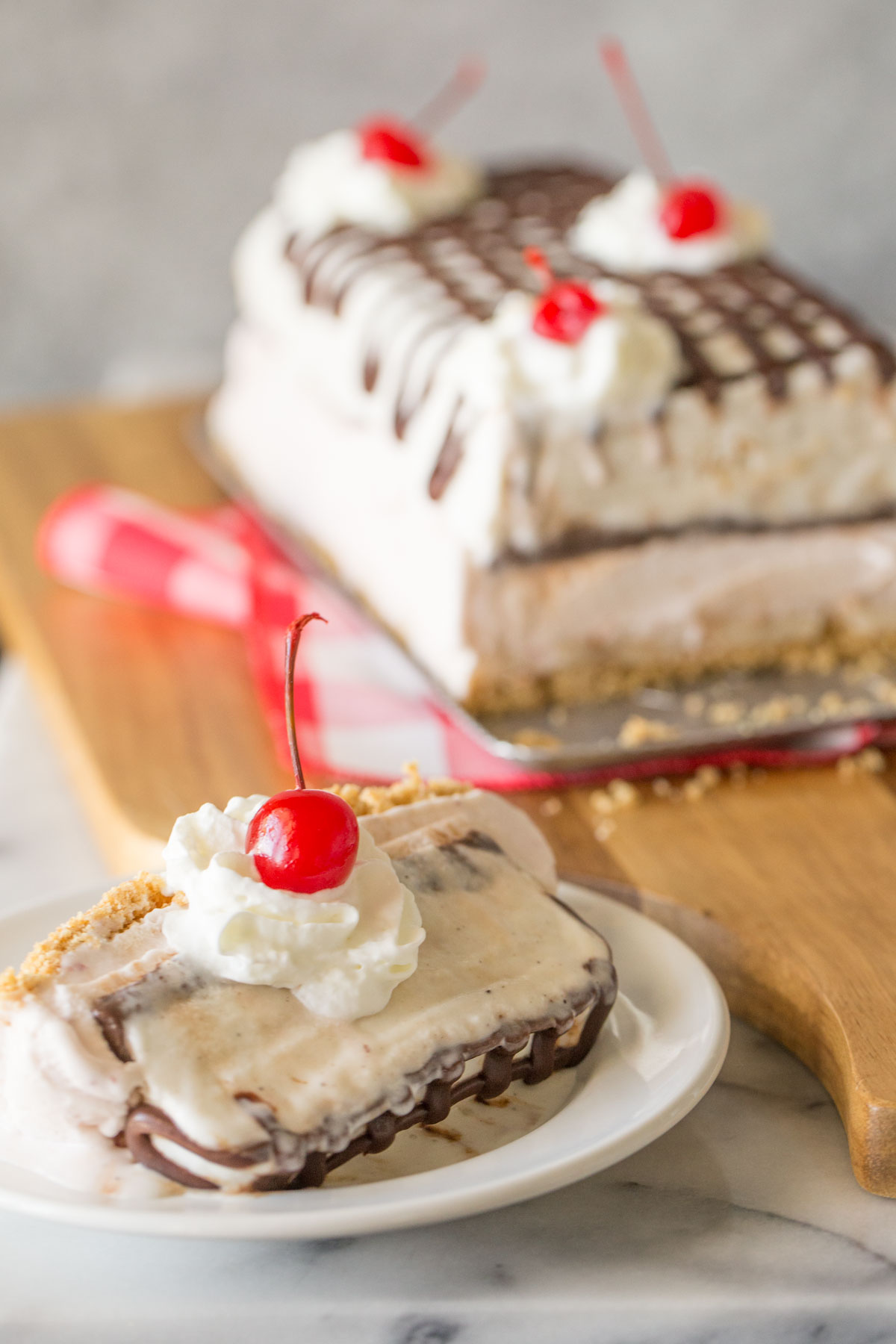 A slice of Banana Split Ice Cream Cake on a plate topped with whipped cream and a cherry, with the rest of the Banana Split Ice Cream Cake in the background.