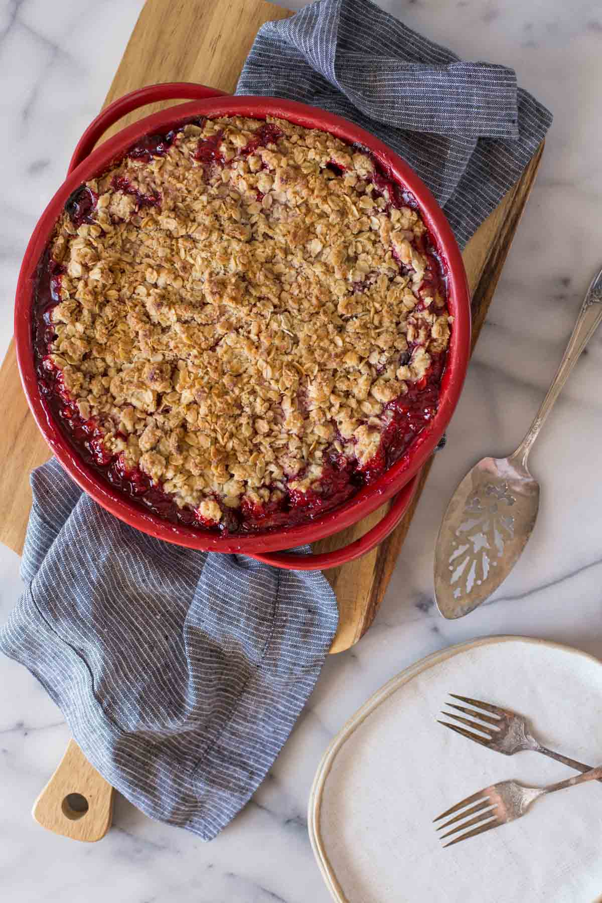 Overhead shot of a whole Berry Crumble Pie on a wooden cutting board.