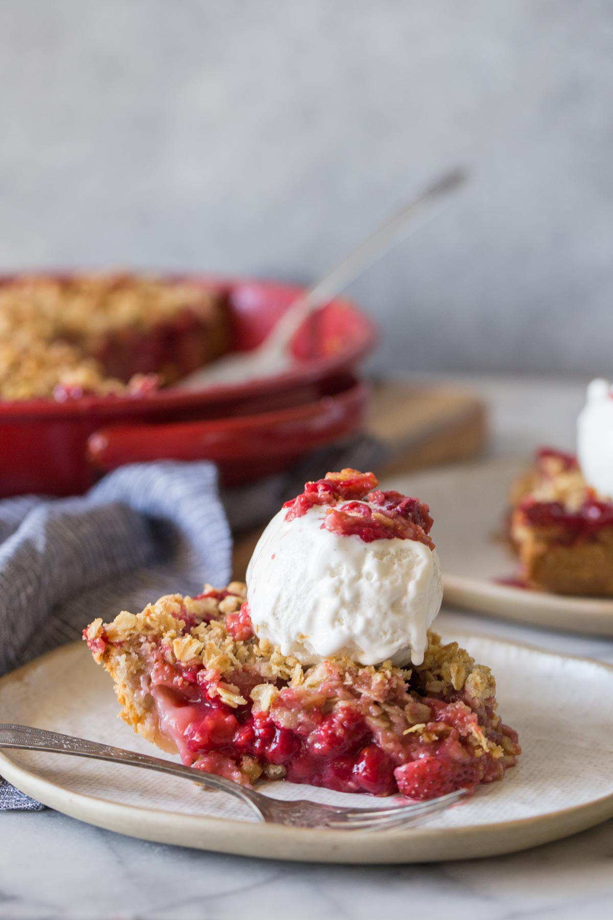A slice of Berry Crumble Pie topped with a scoop of vanilla ice cream.
