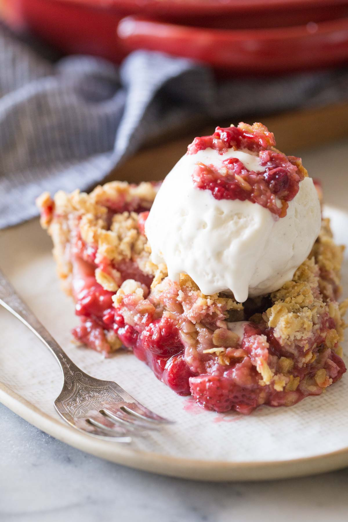 Close up shot of a slice of Berry Crumble Pie topped with a scoop of vanilla ice cream.