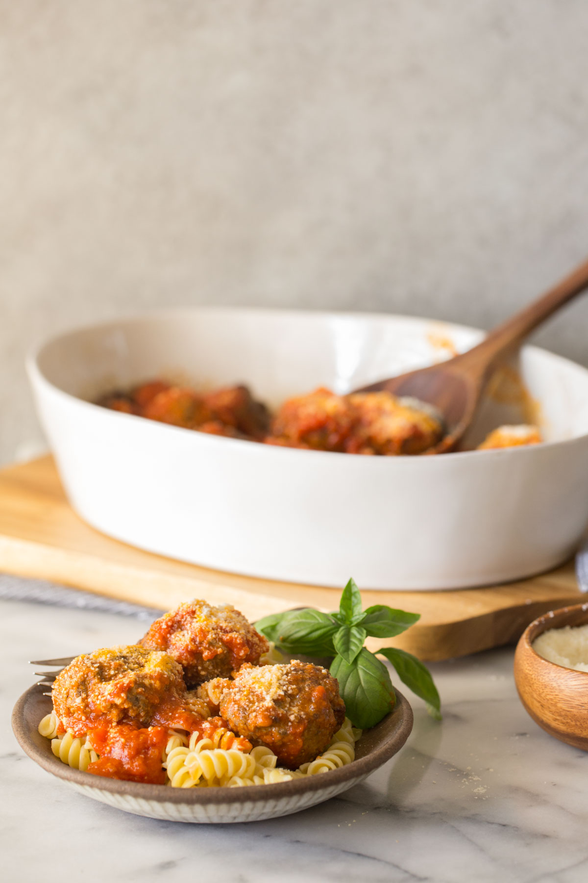 Easy Broiled Italian Meatballs served over rotini pasta in a bowl, with a baking dish of more meatballs in the background.