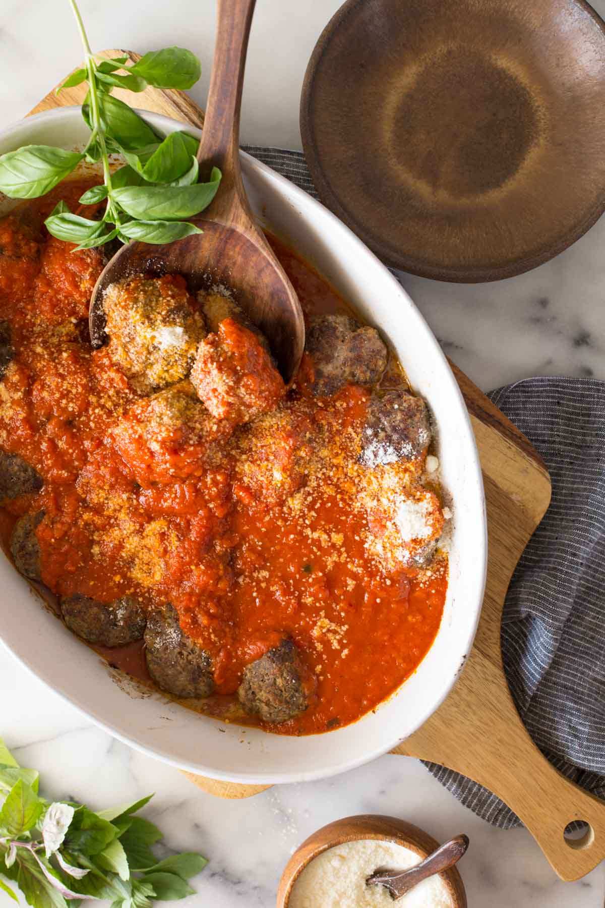 Overhead shot of Easy Broiled Italian Meatballs in a baking dish sitting on a wooden cutting board, with a wood serving spoon in the meatballs.