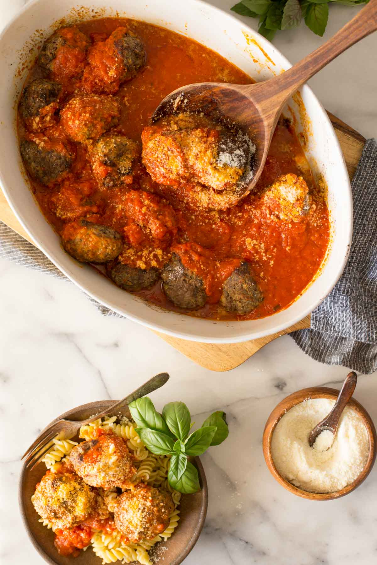 Overhead shot of Easy Broiled Italian Meatballs in a baking dish with a wood serving spoon in the meatballs, and a bowl of meatballs served over rotini pasta and a small wood bowl of Parmesan cheese both next to the cutting board.