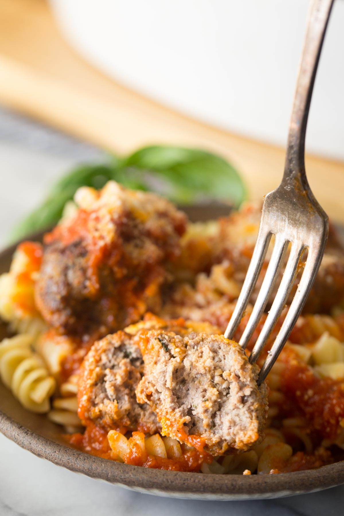 Close up shot of a fork in half of an Easy Broiled Italian Meatball, showing the inside texture, with a bowl of meatballs served over rotini pasta in the background.