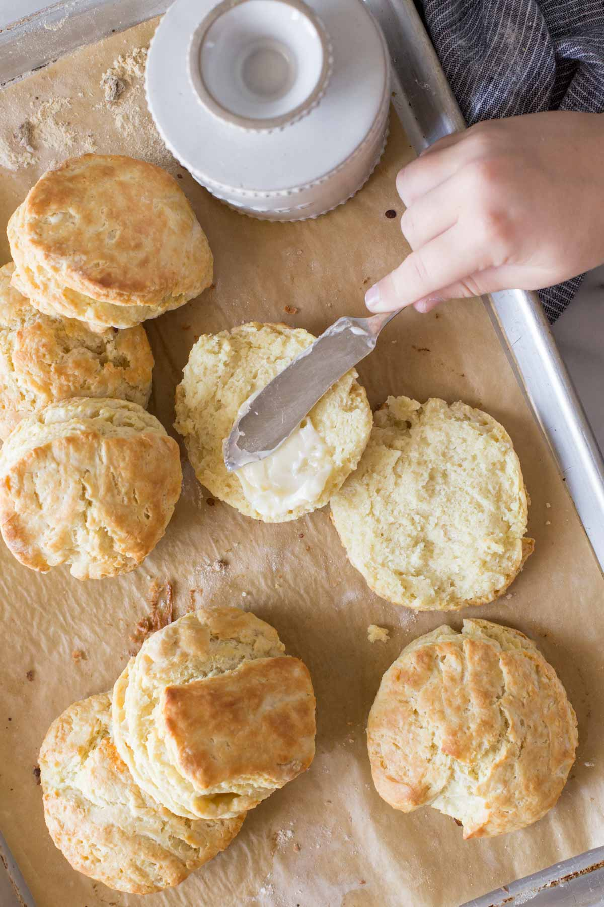 Overhead shot of Easy Homemade Biscuits and a butter dish on a parchment lined baking sheet, with a hand spreading butter on an open biscuit.