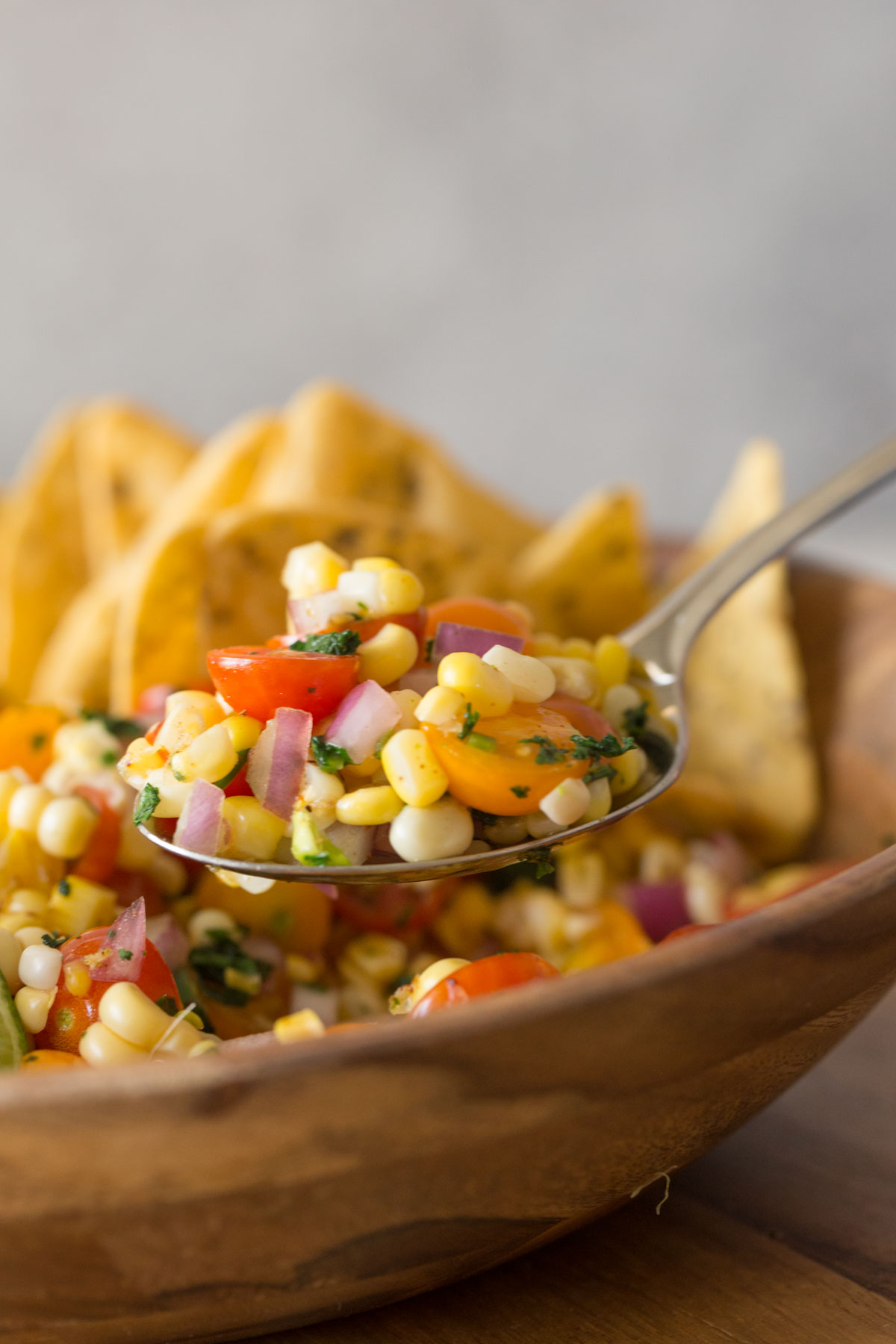 Close up shot of a spoon full of Honey Lime Corn Salsa over the serving bowl.