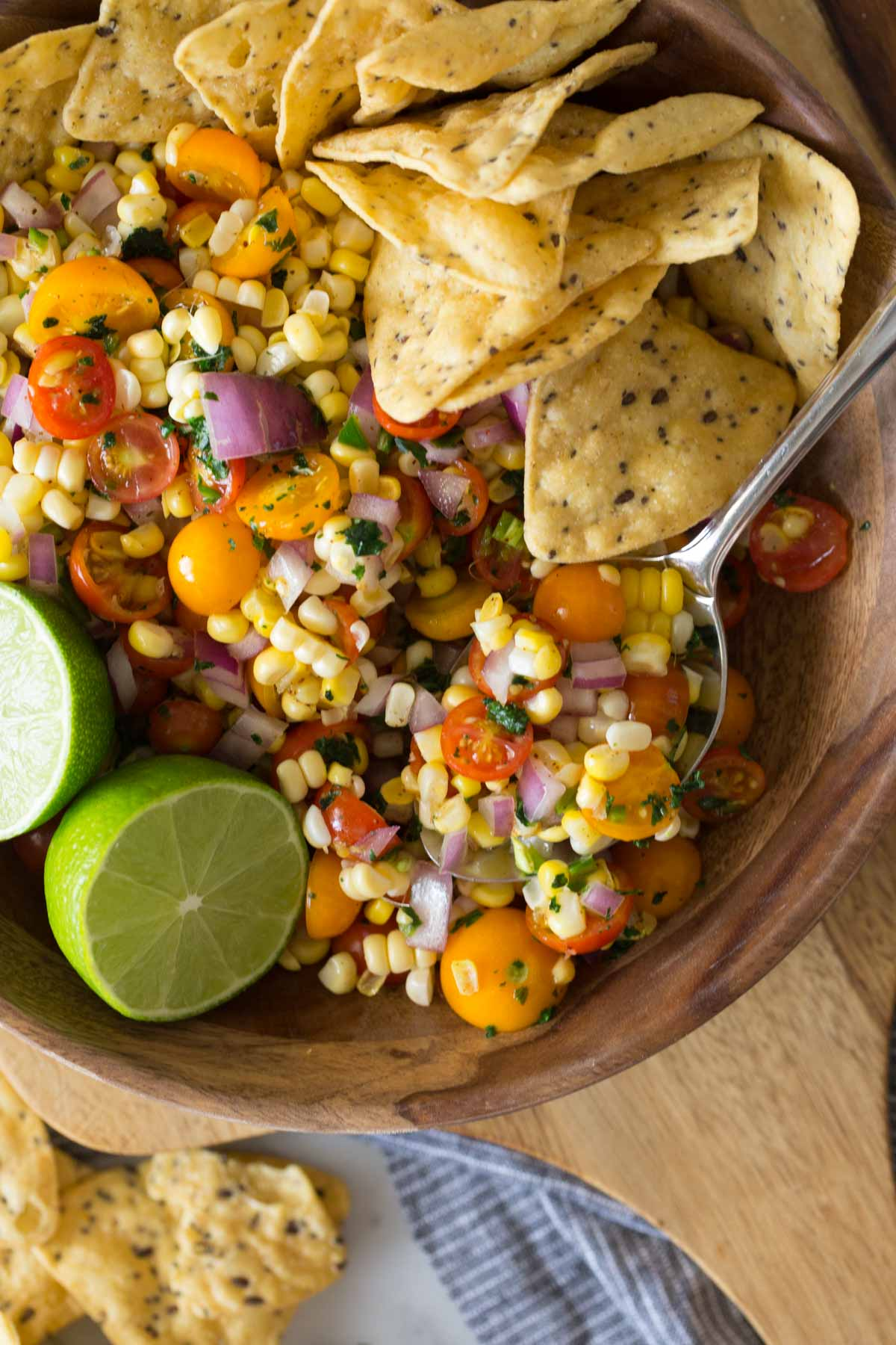 Overhead shot of Honey Lime Corn Salsa in a wood serving bowl with a sliced lime and tortilla chips.