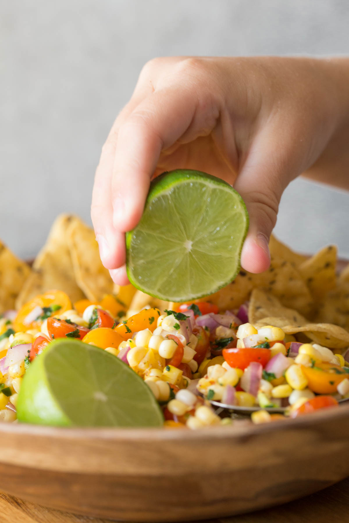 Close up shot of a hand squeezing a lime over a wooden bowl of Honey Lime Corn Salsa.