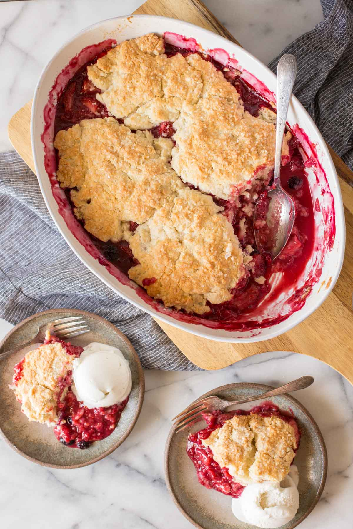 Overhead shot of Triple Berry Cobbler in a baking dish, with two plates of Triple Berry Cobbler each with a scoop of vanilla ice cream next to the baking dish.