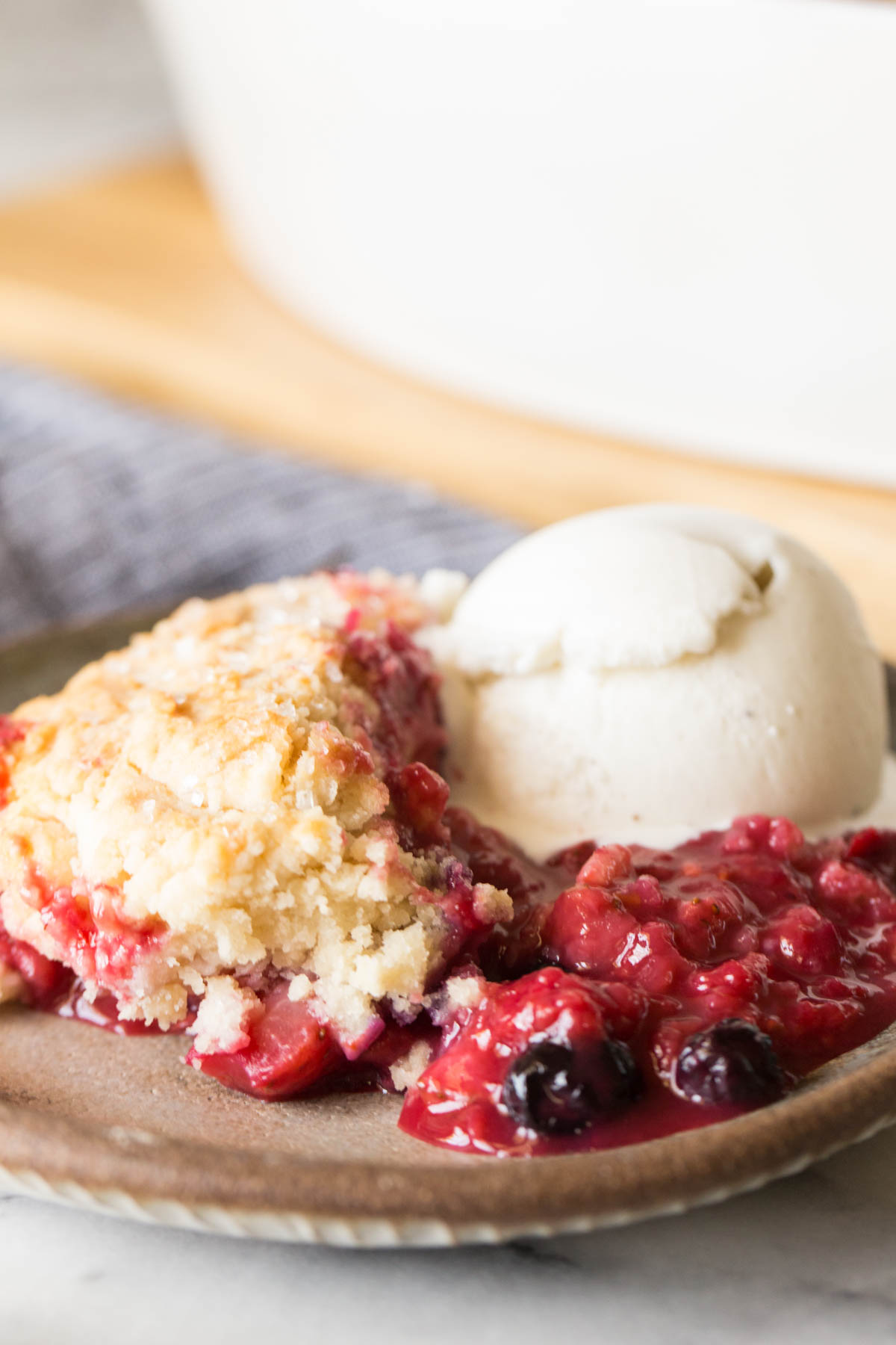 Close up shot of Triple Berry Cobbler on a plate with a scoop of vanilla ice cream.