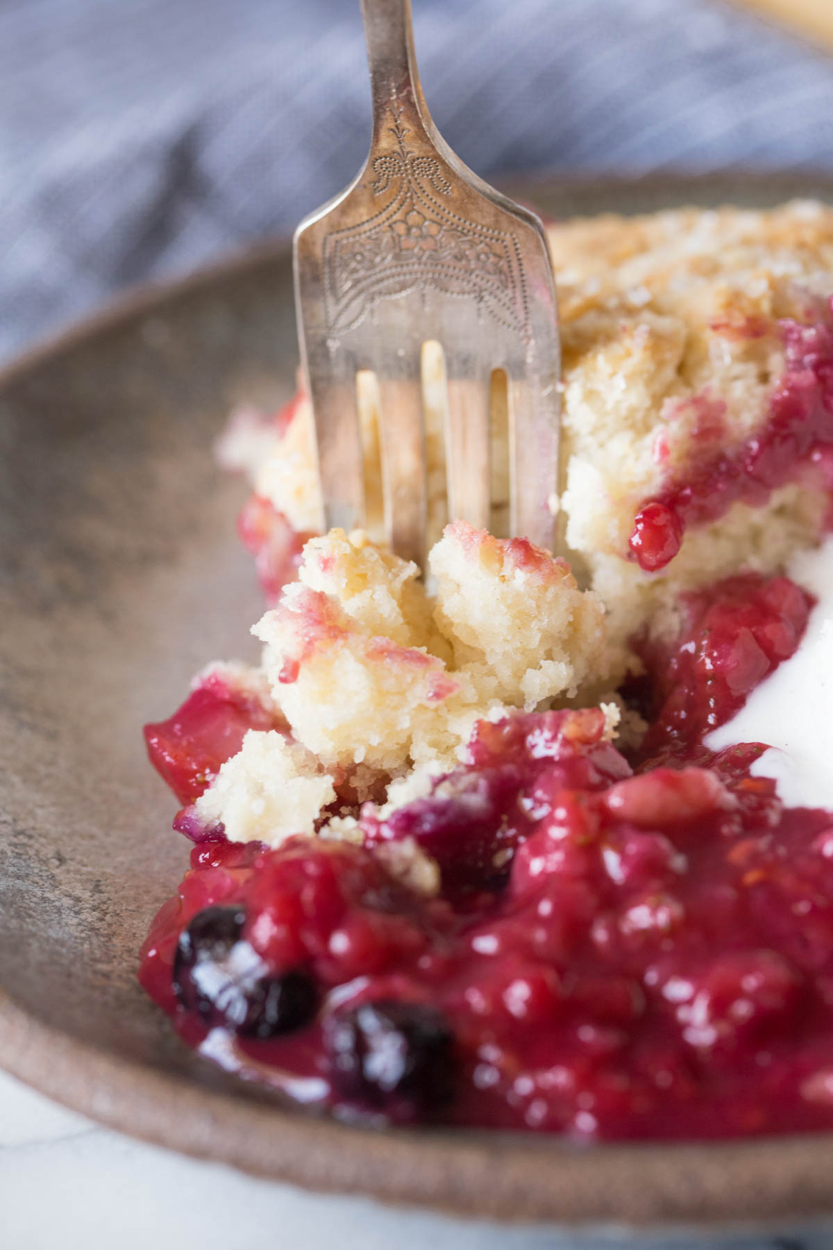 Close up shot of a fork in the Triple Berry Cobbler on a plate.