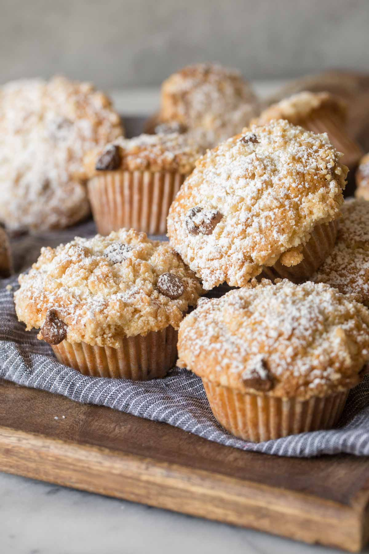 Close up shot of Chocolate Chip Muffins on a blue cloth on top of a wood cutting board.