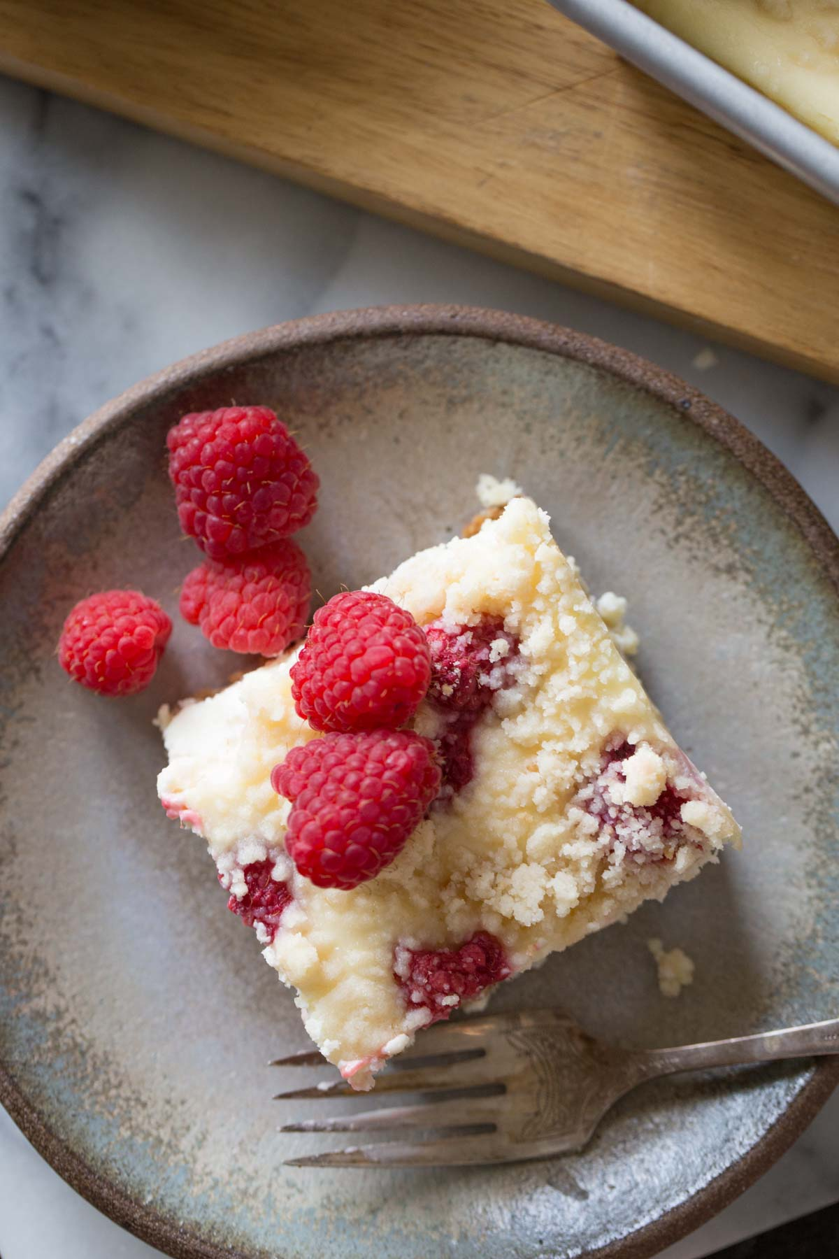 Overhead shot of a Cheesecake Bar With Berry Streusel on a plate with a fork, topped with fresh raspberries.