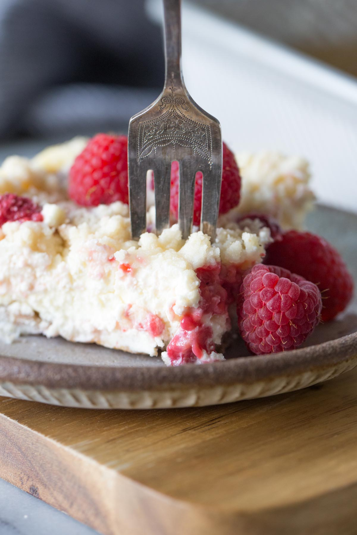 Close up shot of a fork in a Cheesecake Bar With Berry Streusel on a plate.