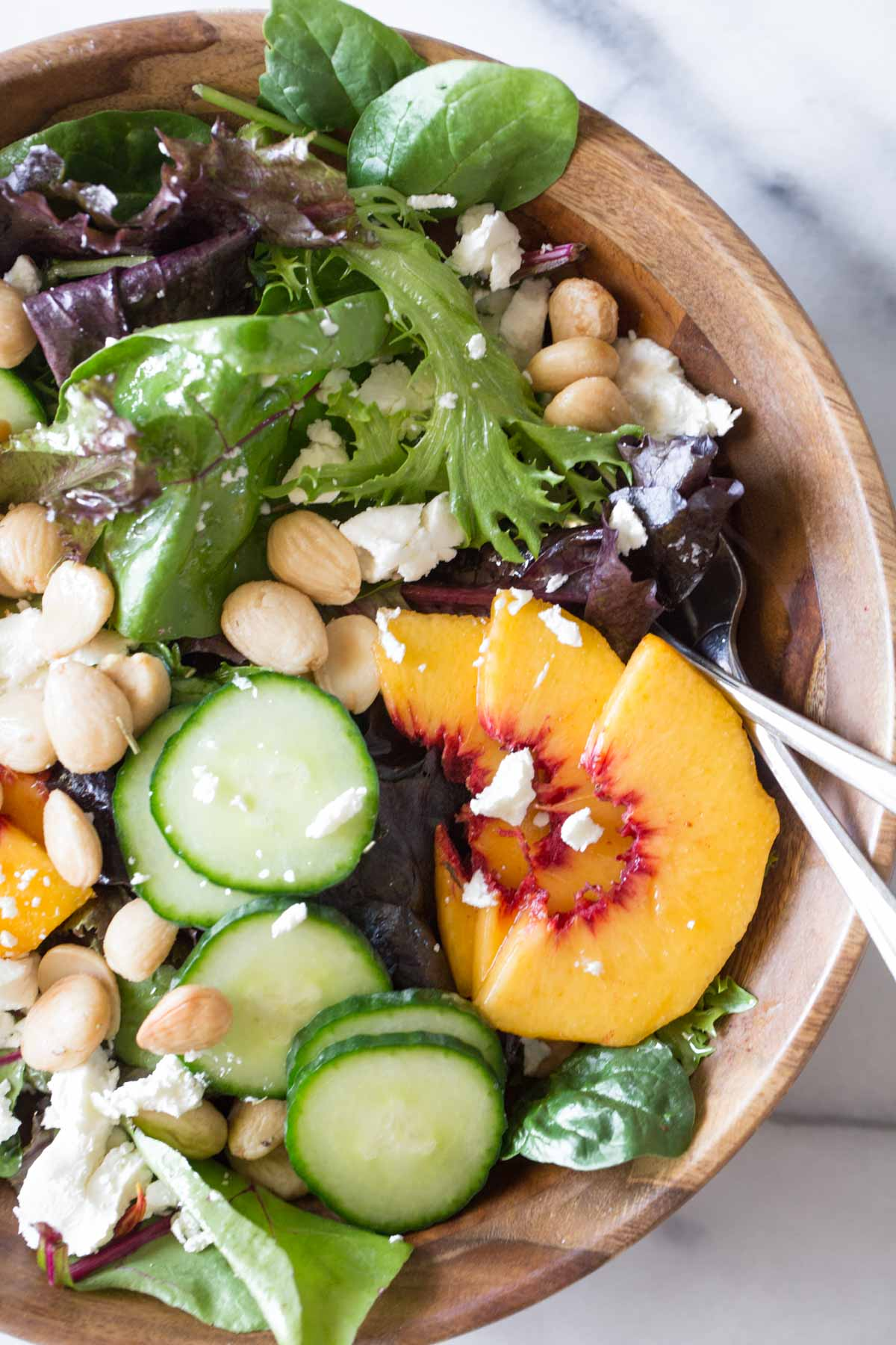 Close up shot of Summer Peach Salad in a wood bowl.