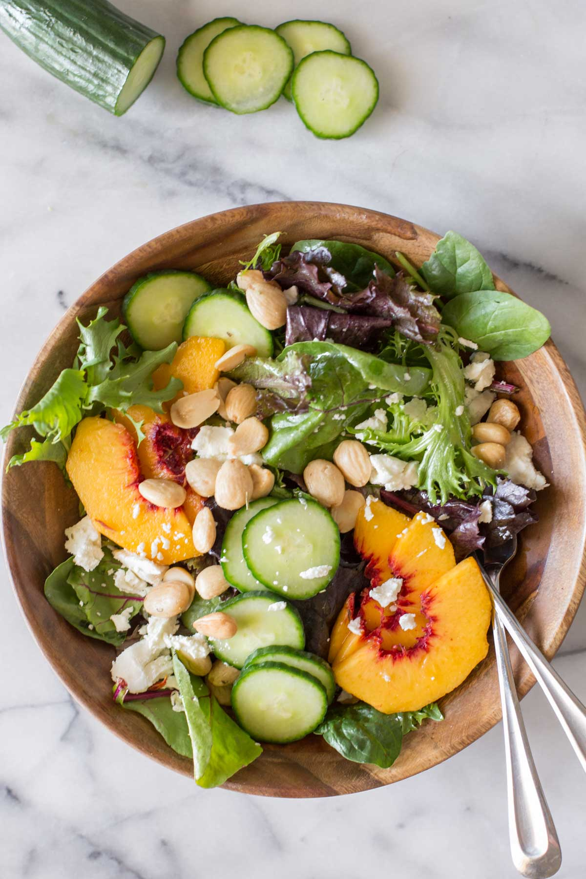 Overhead shot of Summer Peach Salad in a wood bowl on a marble background with a sliced cucumber next to the bowl.