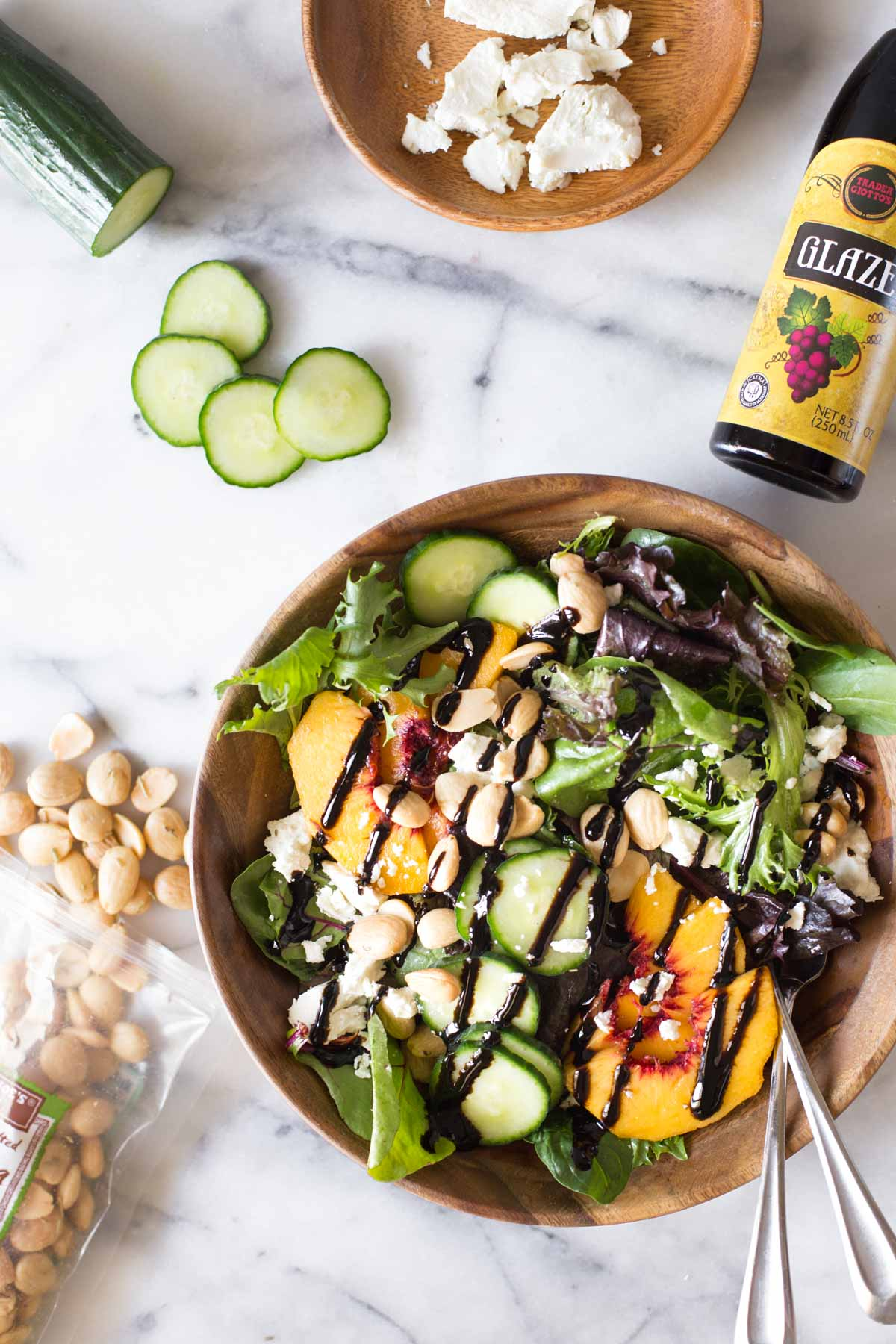 Overhead shot of Summer Peach Salad in a wood bowl on a marble background with ingredients of the salad around the bowl.