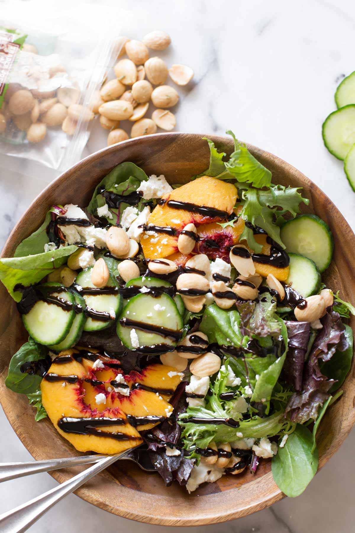 Overhead shot of Summer Peach Salad in a wood bowl on a marble background.