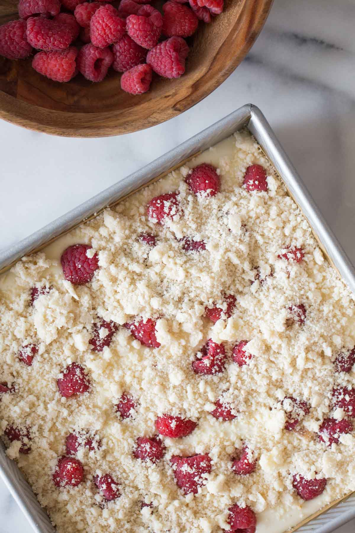 Overhead shot of Cheesecake Bars With Berry Streusel in a baking pan, next to a wooden bowl of fresh raspberries.