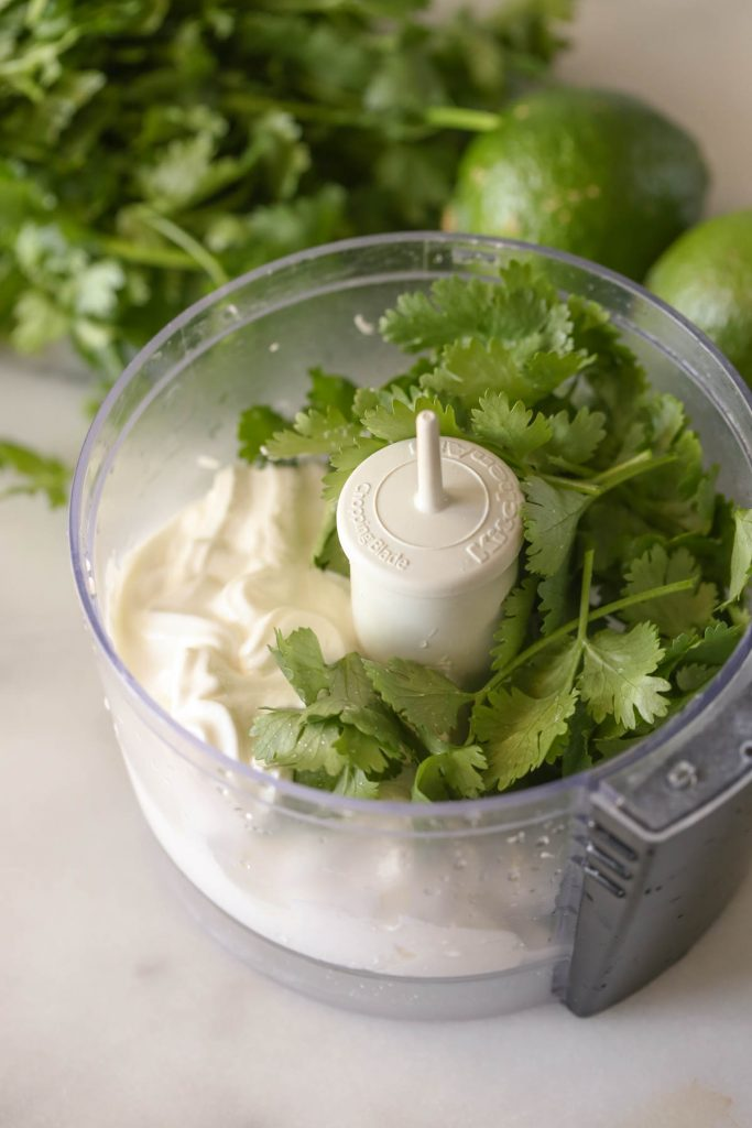 A small food processor with the ingredients for the Cilantro Lime Cream in it.