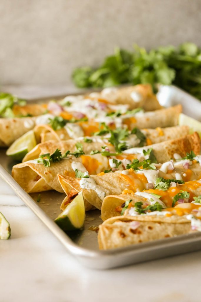 BBQ Chicken Taquitos garnished with fresh cilantro and lime wedges on a baking sheet.