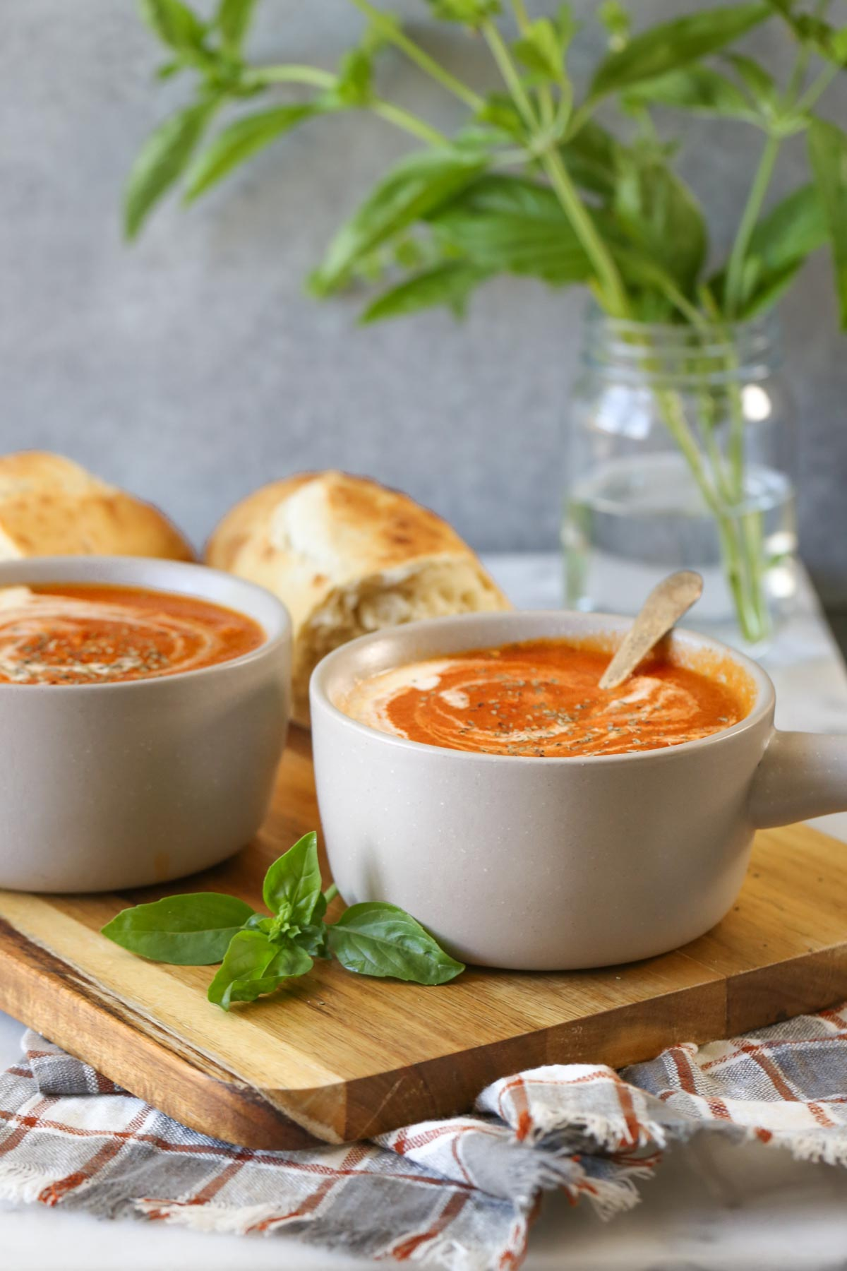 Two bowls of Creamy Balsamic Tomato Soup on a wood cutting board with two torn pieces of crusty bread.