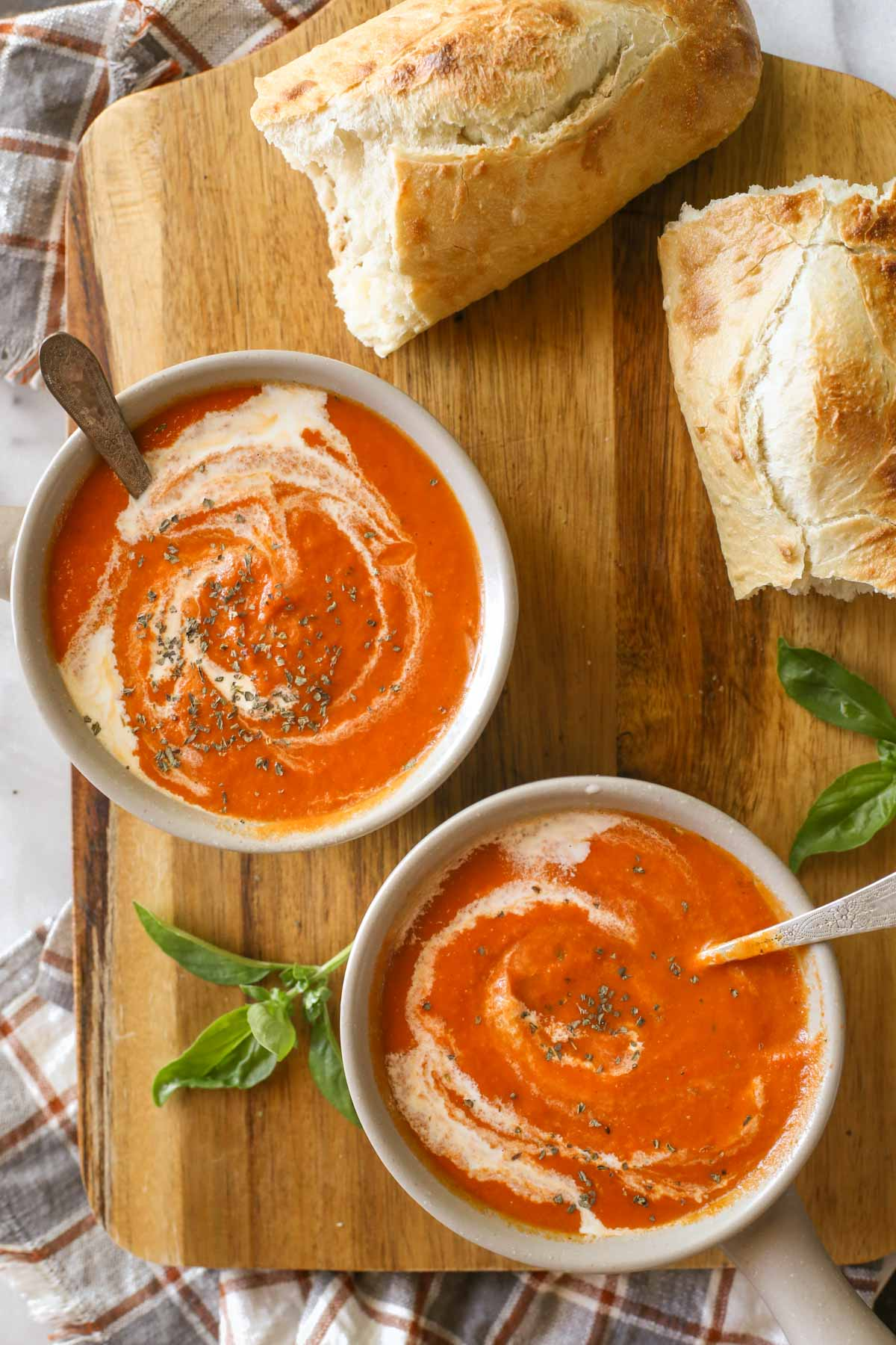 Overhead shot of two bowls of Creamy Balsamic Tomato Soup on a wood cutting board, along with two pieces of torn crusty bread.