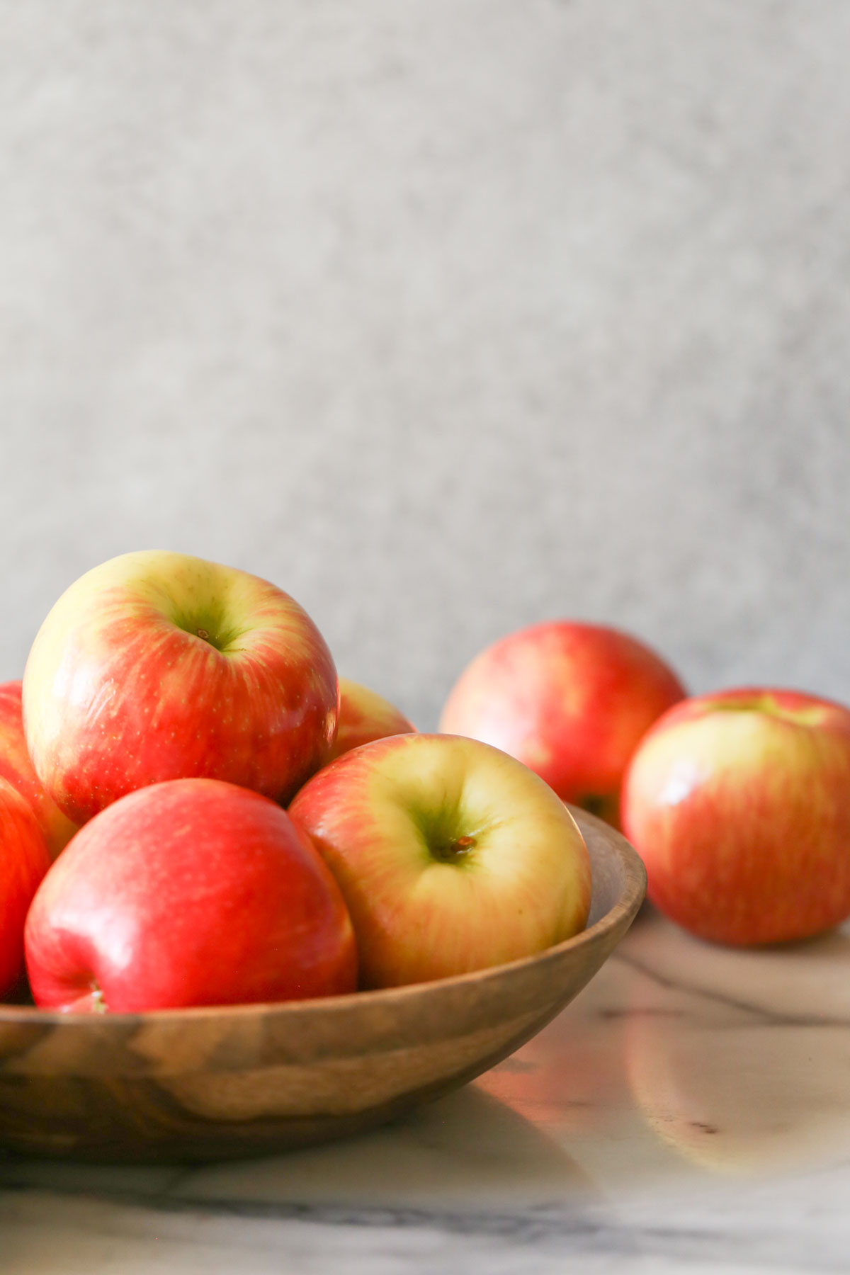 A wood bowl full of apples.
