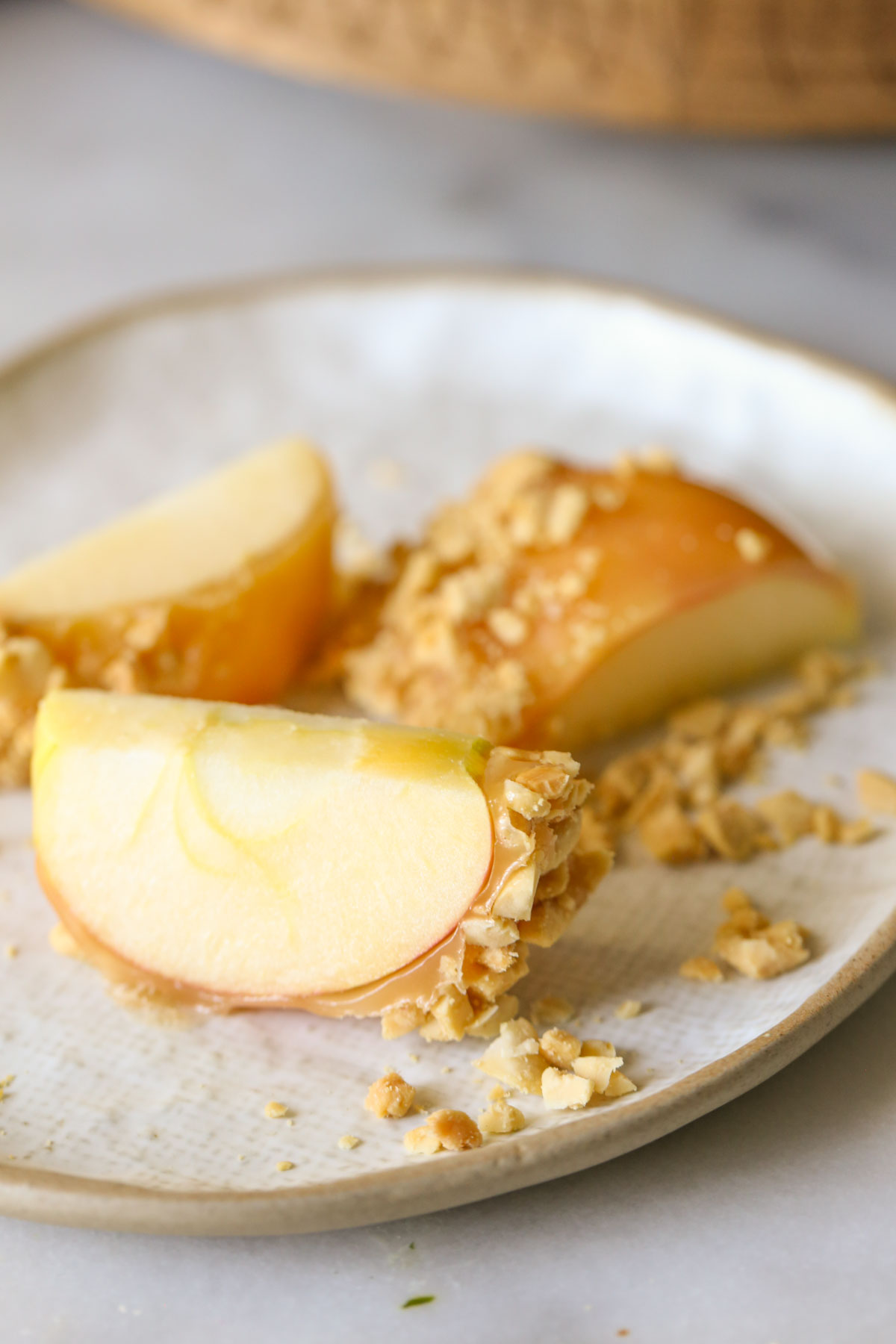 Close up shot of a sliced Homemade Caramel Apple on a plate.