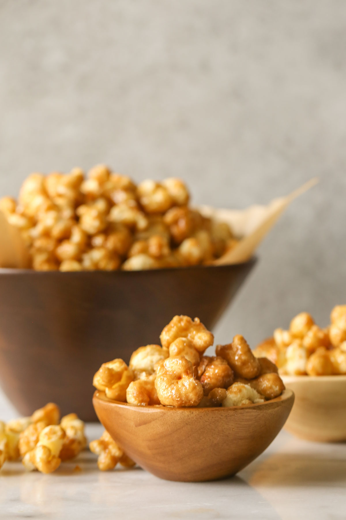 A small wood bowl of Caramel Puff Corn, with another small bowl and a large wood bowl of Caramel Puff Corn in the background.