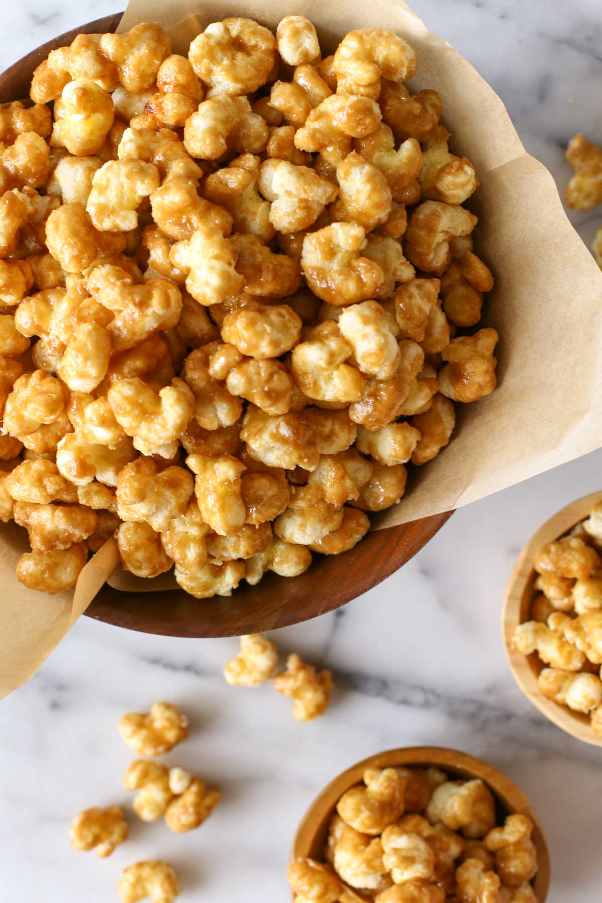Overhead shot of Caramel Puff Corn in a wood bowl lined with parchment paper, with two small wood bowls of Caramel Puff Corn next to it.