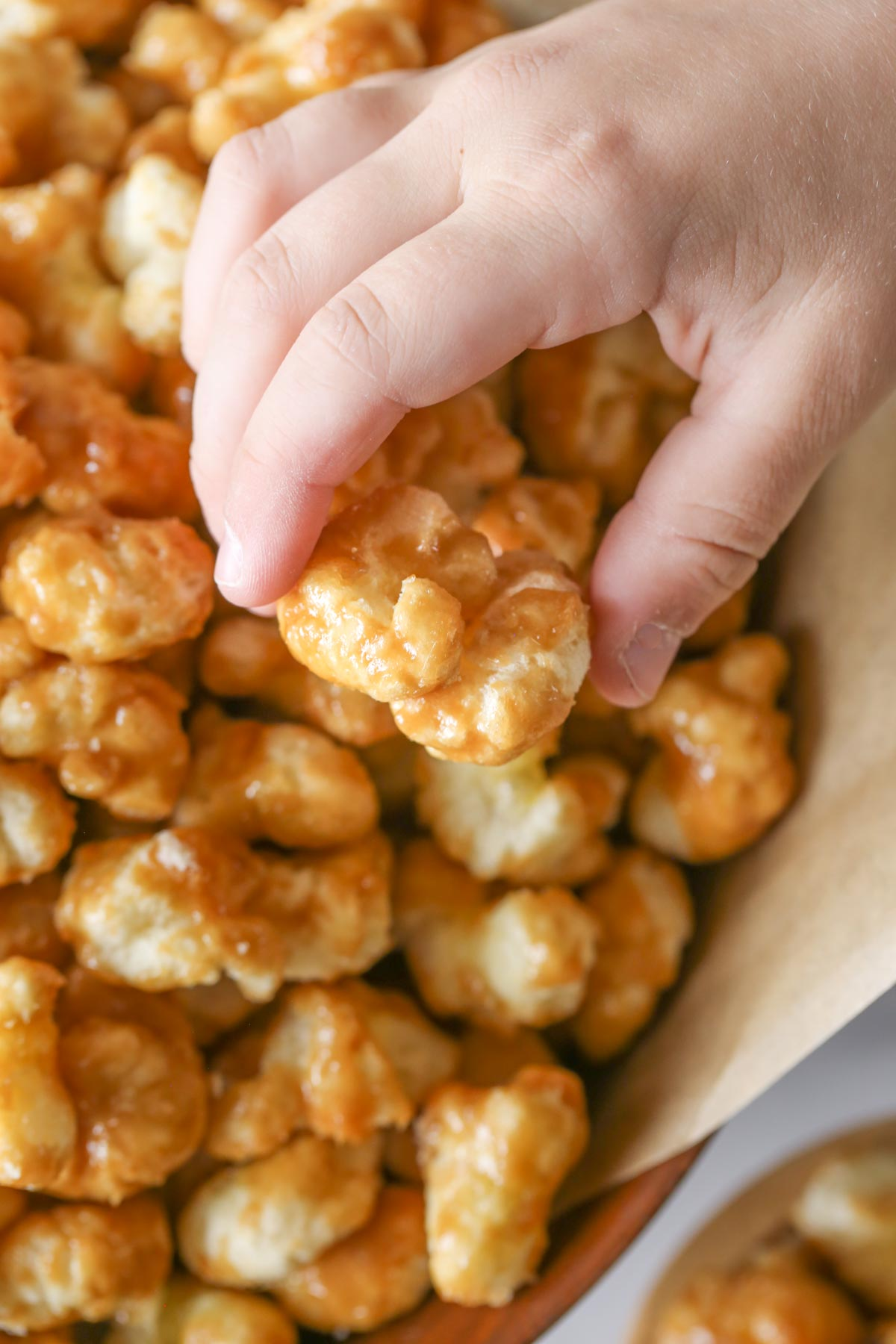 Close up shot of a hand grabbing Caramel Puff Corn from a wood bowl lined with parchment paper.