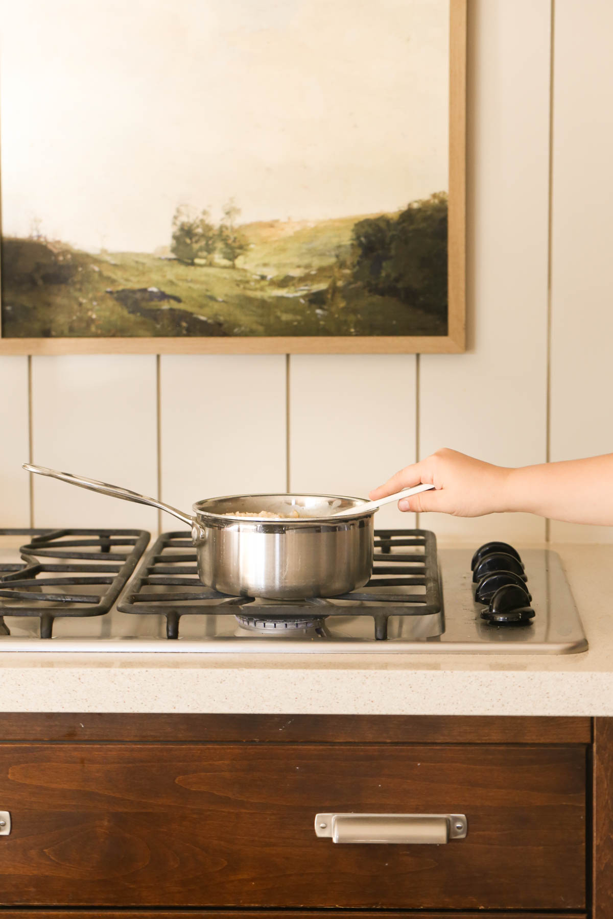 A pot of oatmeal on a gas stove top with a hand on the stirring utensil.