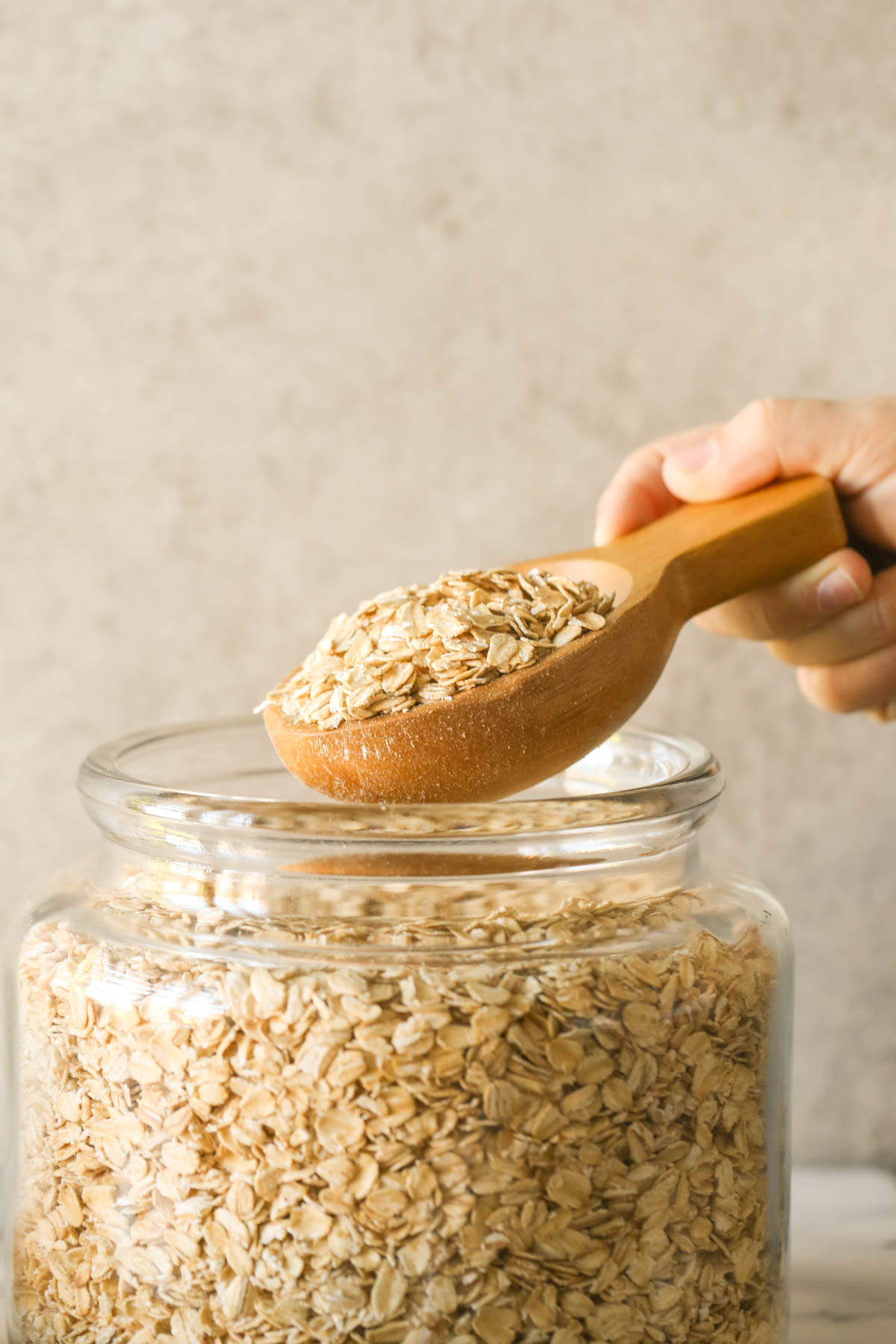 A large wooden scoop full of oats being held above a large glass jar of old fashioned oats.