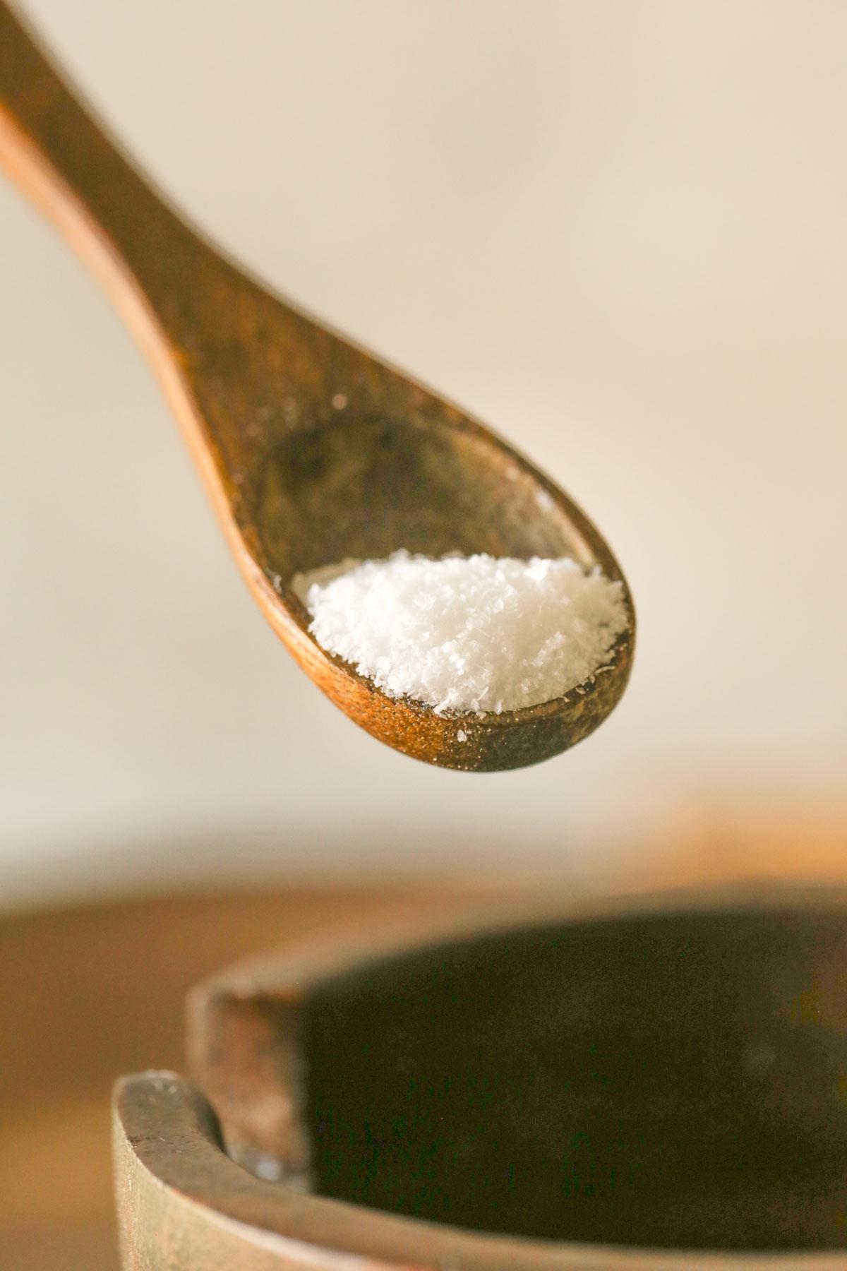 Close up shot of a wooden teaspoon of salt.