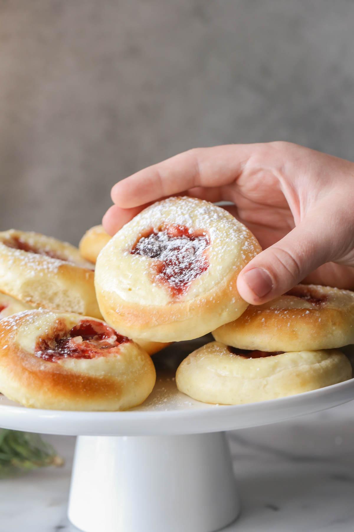 A hand grabbing a Raspberry Cream Cheese Kolache from the cake stand full of Raspberry Cream Cheese Kolaches.