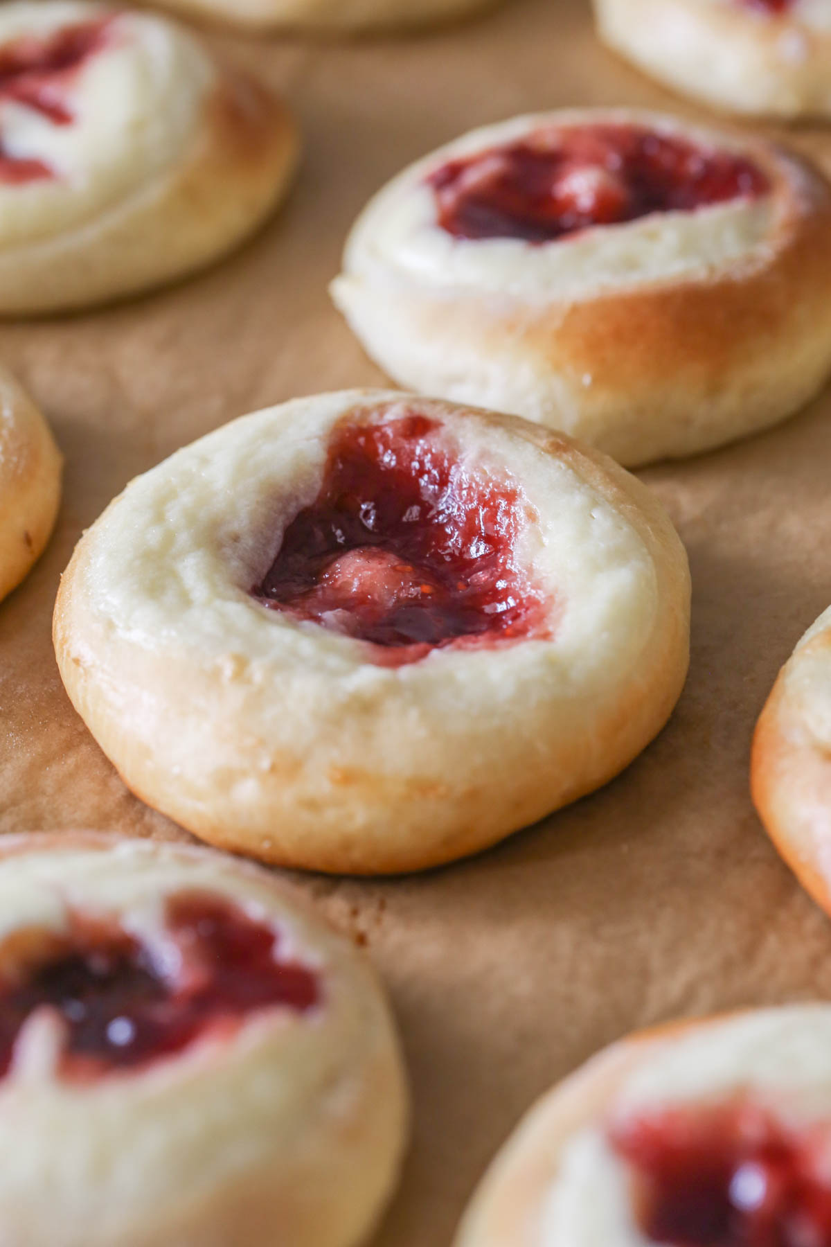 Close up shot of Raspberry Cream Cheese Kolaches on parchment paper after being baked.