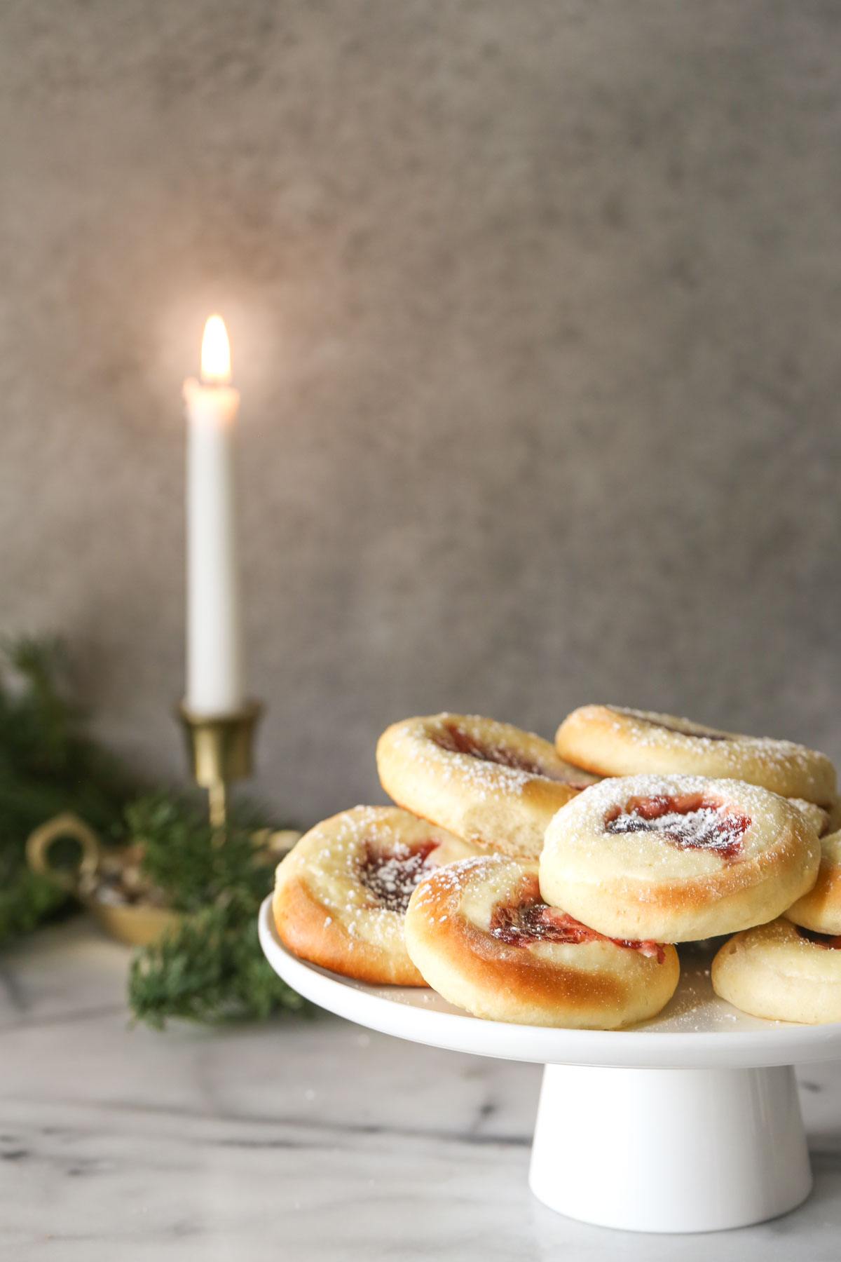 Raspberry Cream Cheese Kolaches arranged on a cake stand, with a candle burning in the background.