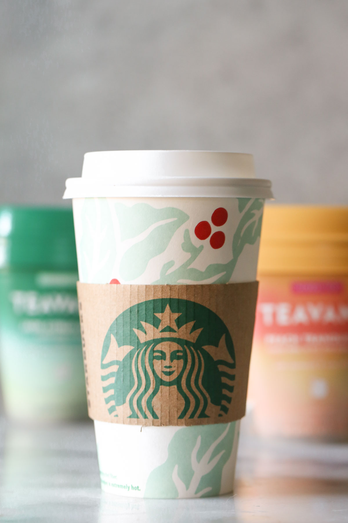 A Starbucks Medicine Ball Tea in a Starbucks hot cup, with the Teavana tea packages in the background.