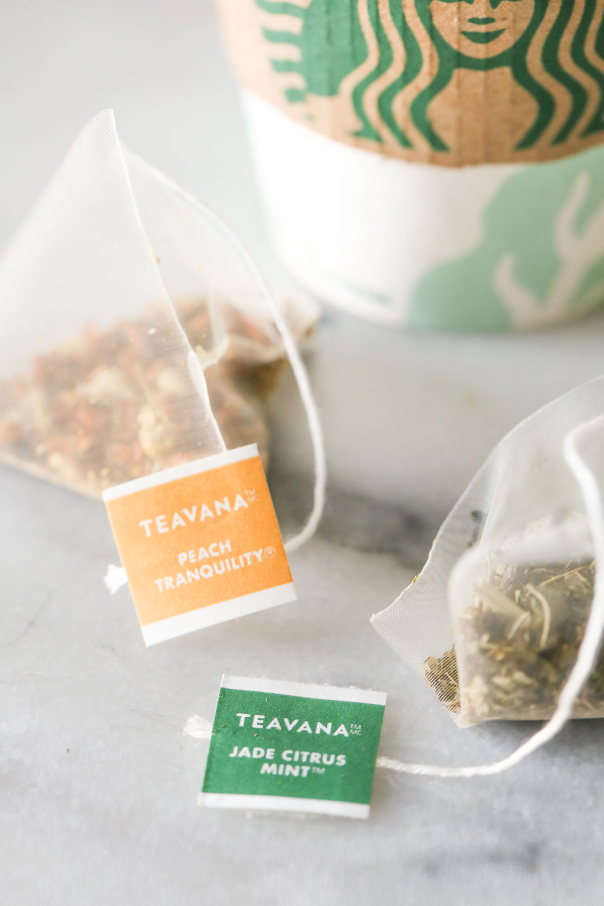 Close up shot of a Teavana Peach Tranquility tea sachet next to a Teavana Jade Citrus Mint tea sachet, with a Starbucks cup in the background.