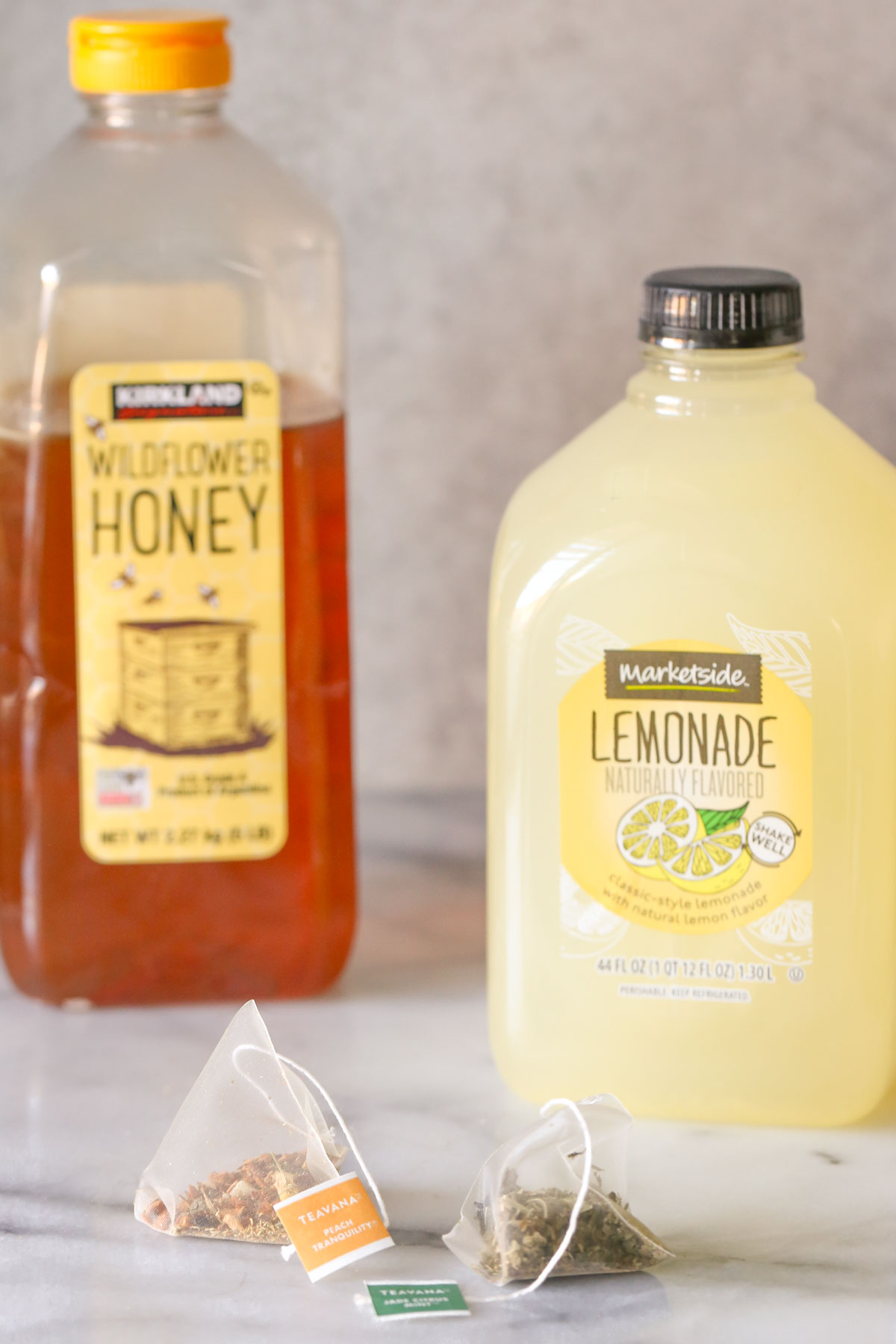 A Teavana Peach Tranquility tea sachet next to a Teavana Jade Citrus Mint tea sachet, with a jug of lemonade and a container of honey in the background, all ingredients for the Starbucks Medicine Ball Tea.