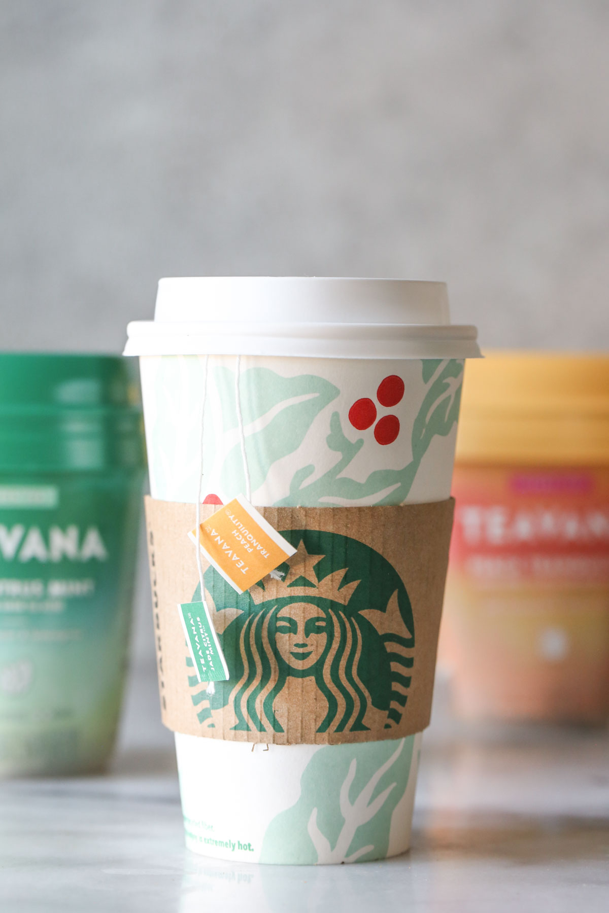 A Starbucks Medicine Ball Tea in a Starbucks hot cup, with the tea bag labels hanging over the side, and the Teavana tea packages in the background.