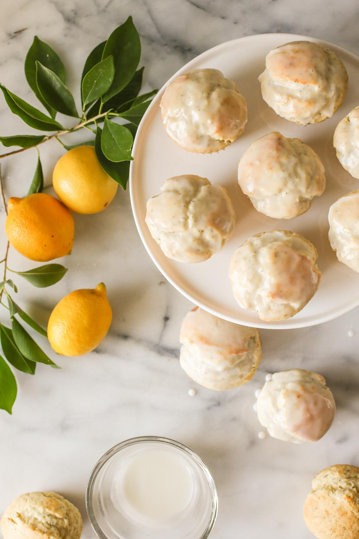Overhead shot of Glazed Lemon Poppy Seed Muffins on a cake stand with two muffins next to the stand and two unglazed muffins next to a glass bowl of glaze, all on a marble background with a branch from a lemon tree and three whole lemons.