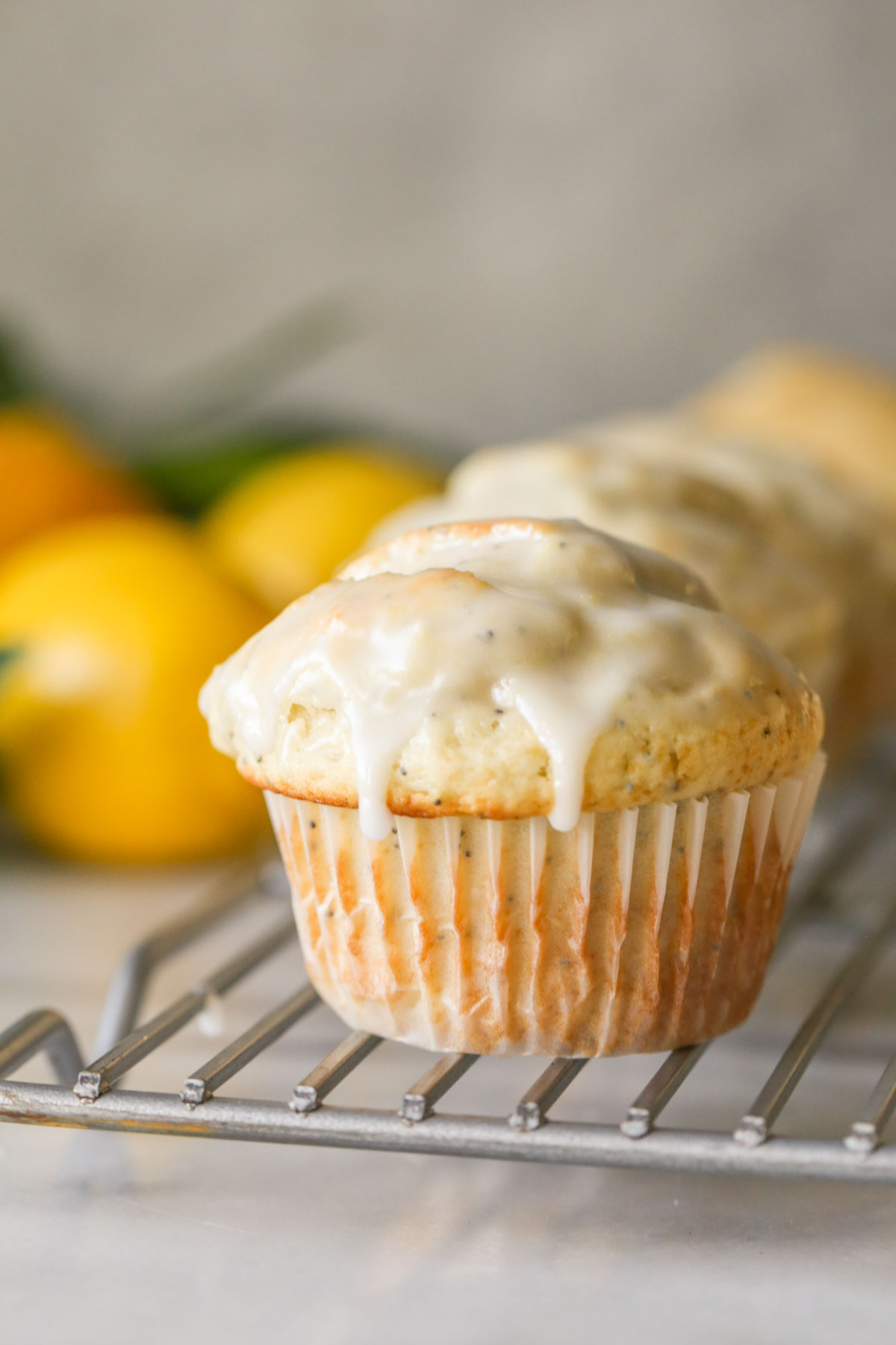 Close up shot of a Glazed Lemon Poppy Seed Muffin on a cooling rack.