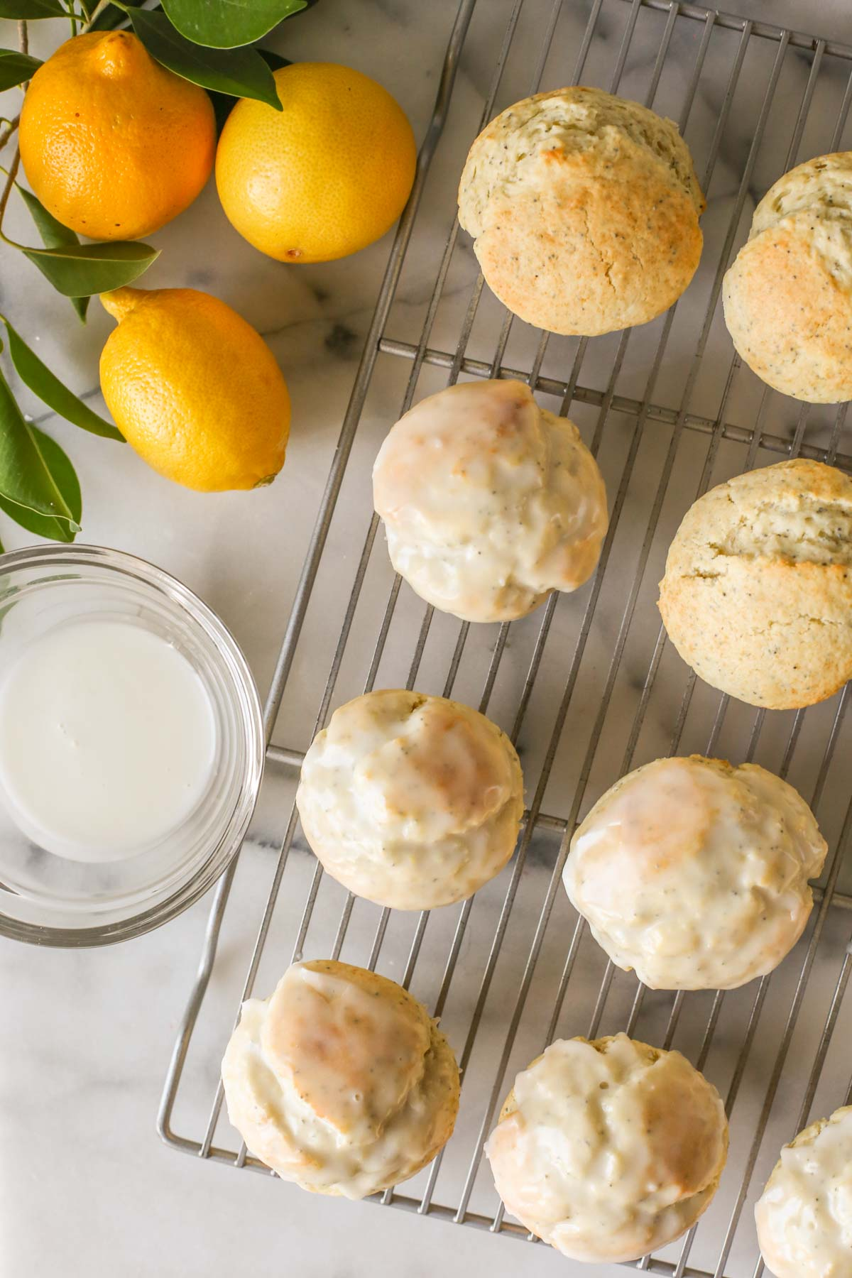 Overhead shot of Lemon Poppy Seed Muffins on a cooling rack, some glazed and some not yet glazed, with a glass bowl of glaze next to the cooling rack, along with a branch from a lemon tree and three whole lemons.