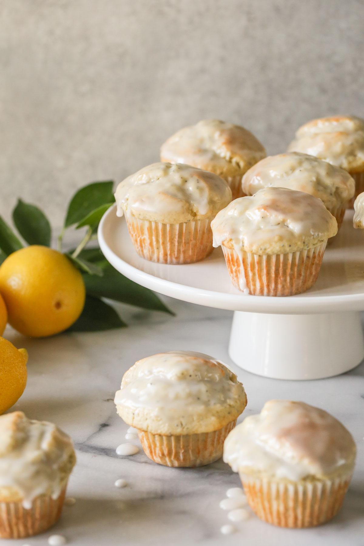 Glazed Lemon Poppy Seed Muffins on a cake stand with three muffins next to the stand, along with a branch from a lemon tree and whole lemons.
