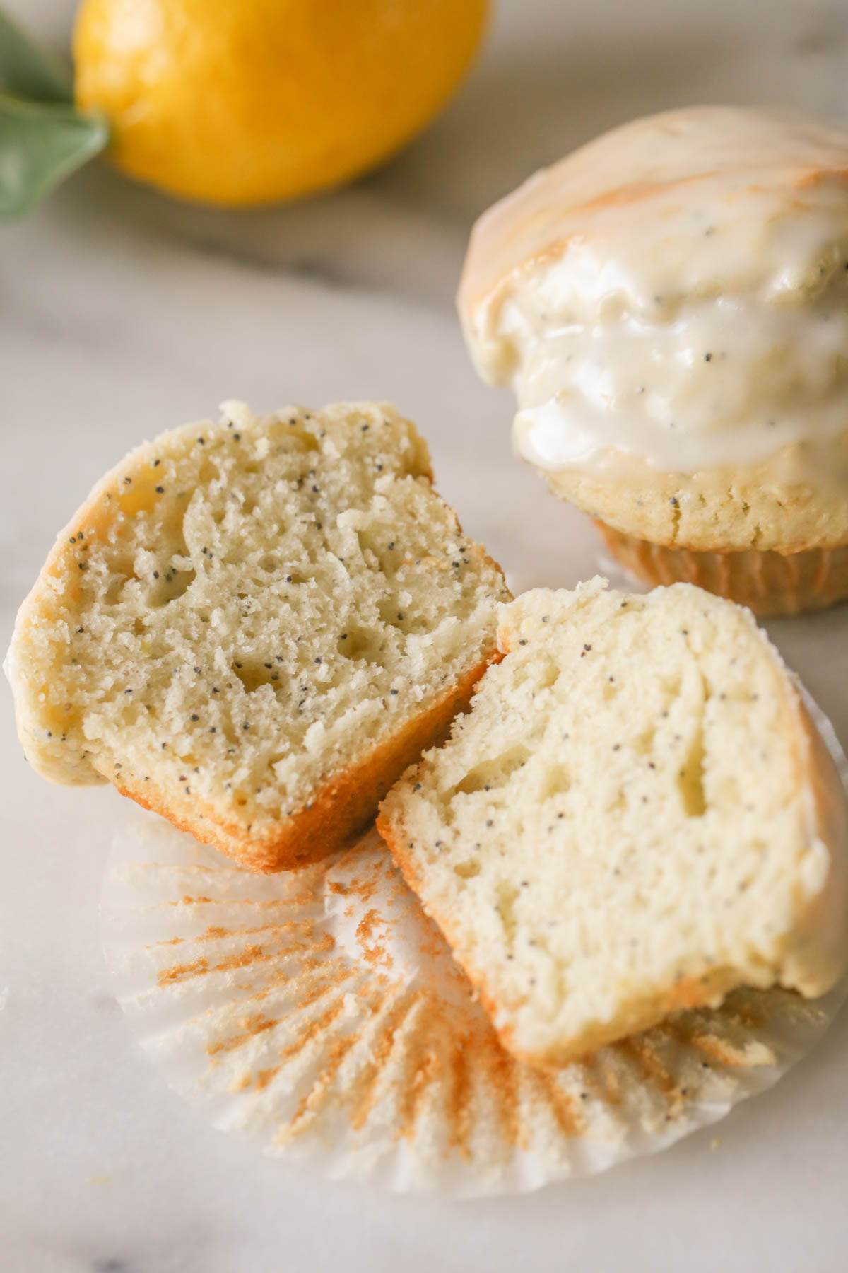 A Glazed Lemon Poppy Seed Muffin sliced in half, placed on the muffin liner, with another whole muffin next to it and a whole lemon in the background.